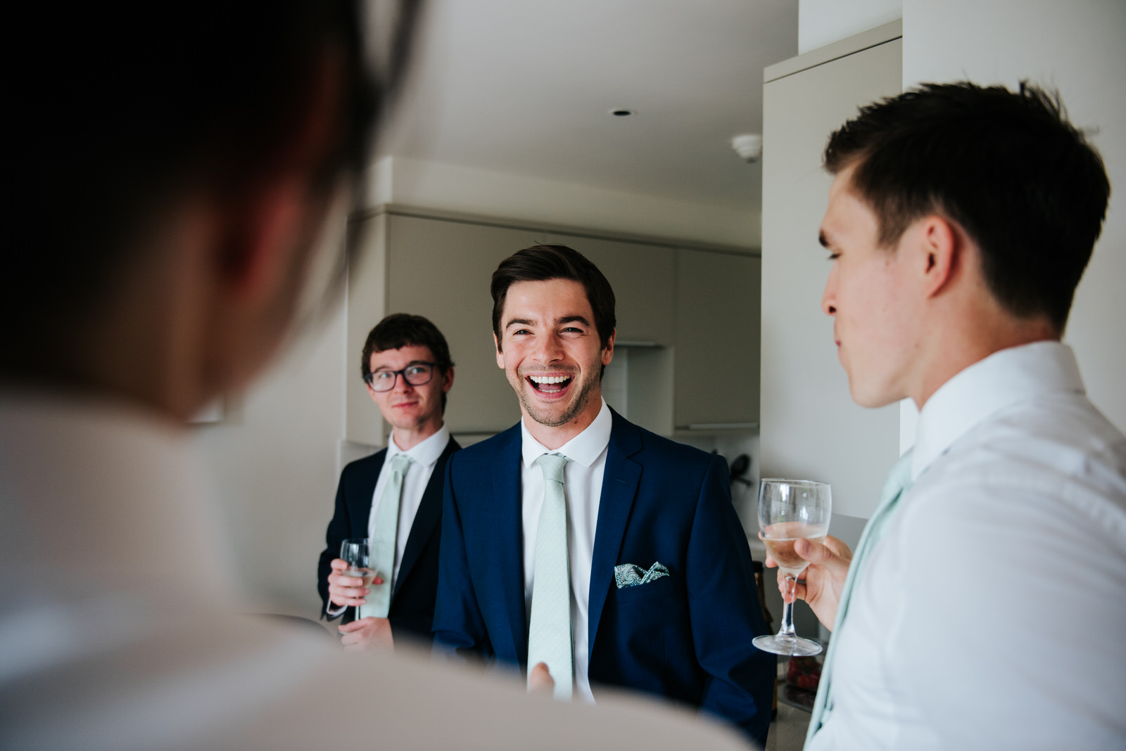 Groom and groomsmen laugh while sharing emotional advice before