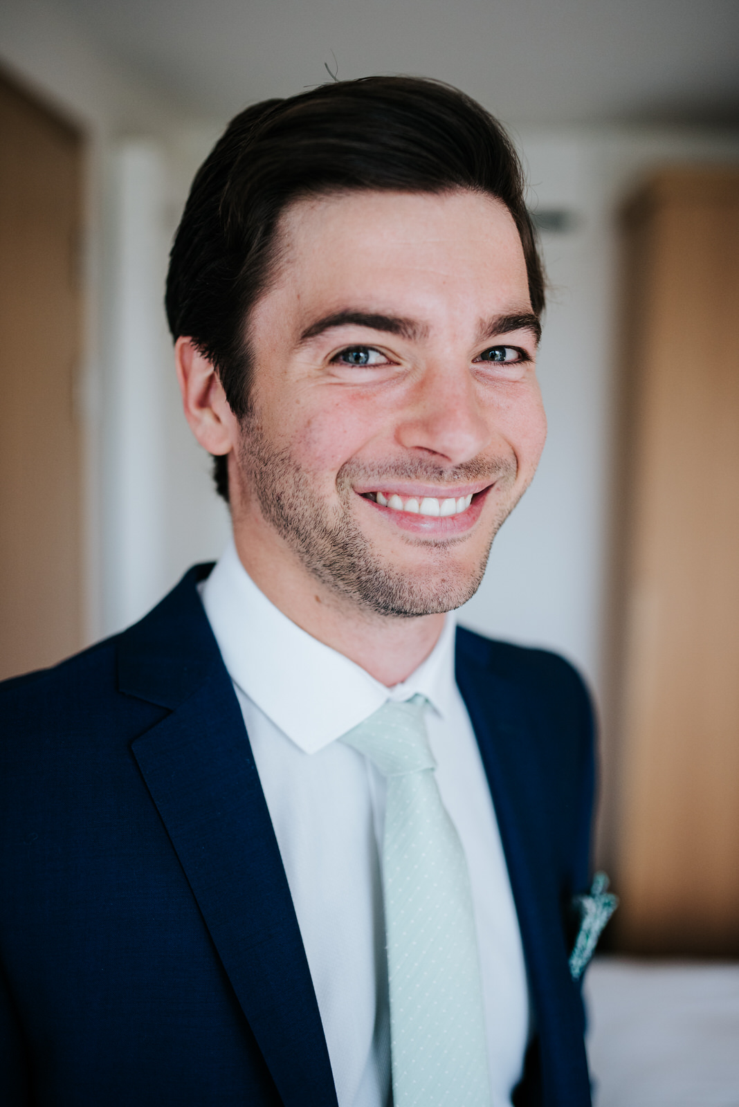 Portrait of groom looking into camera during wedding preparation