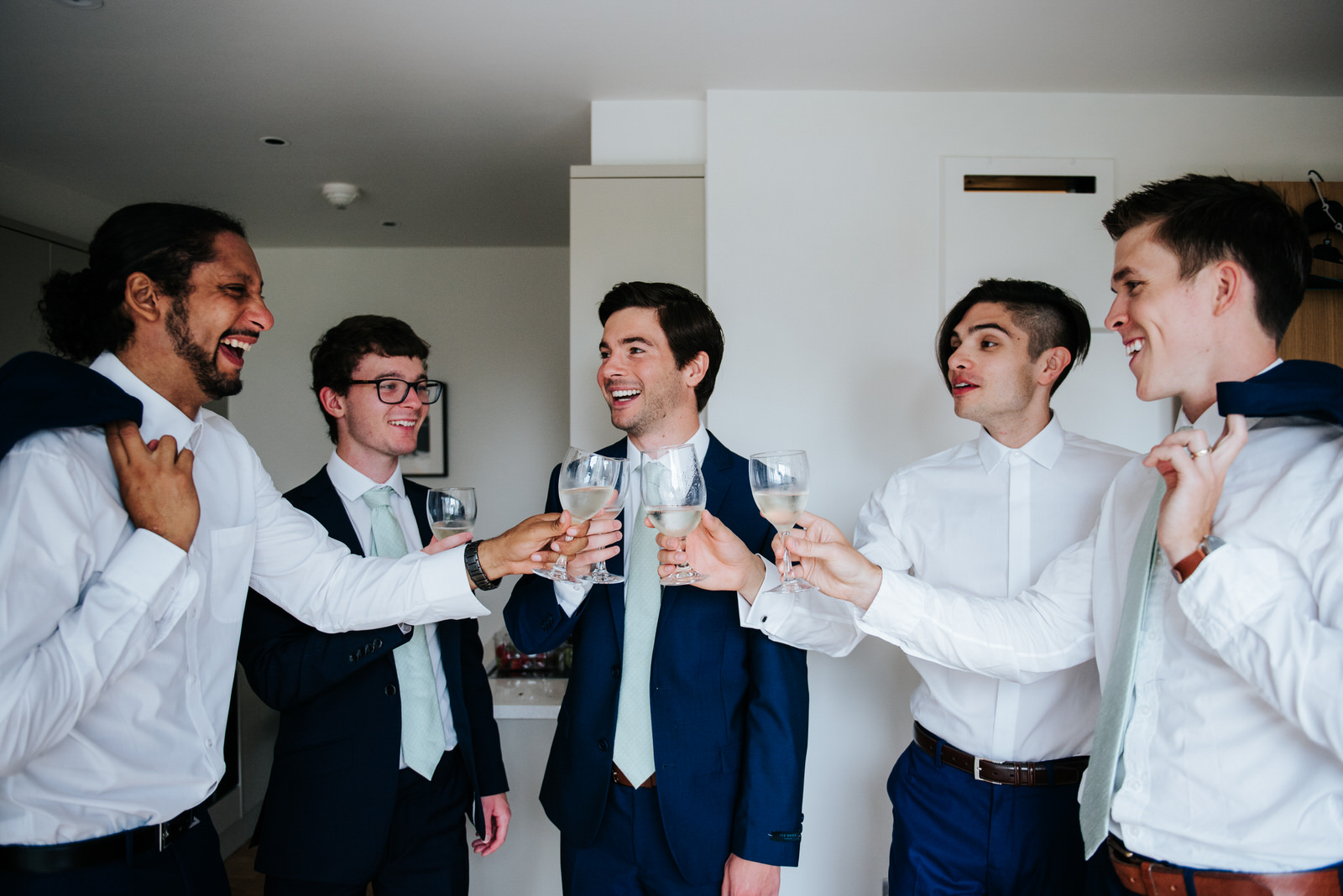 Groom and groomsmen share a toast as they finish getting ready