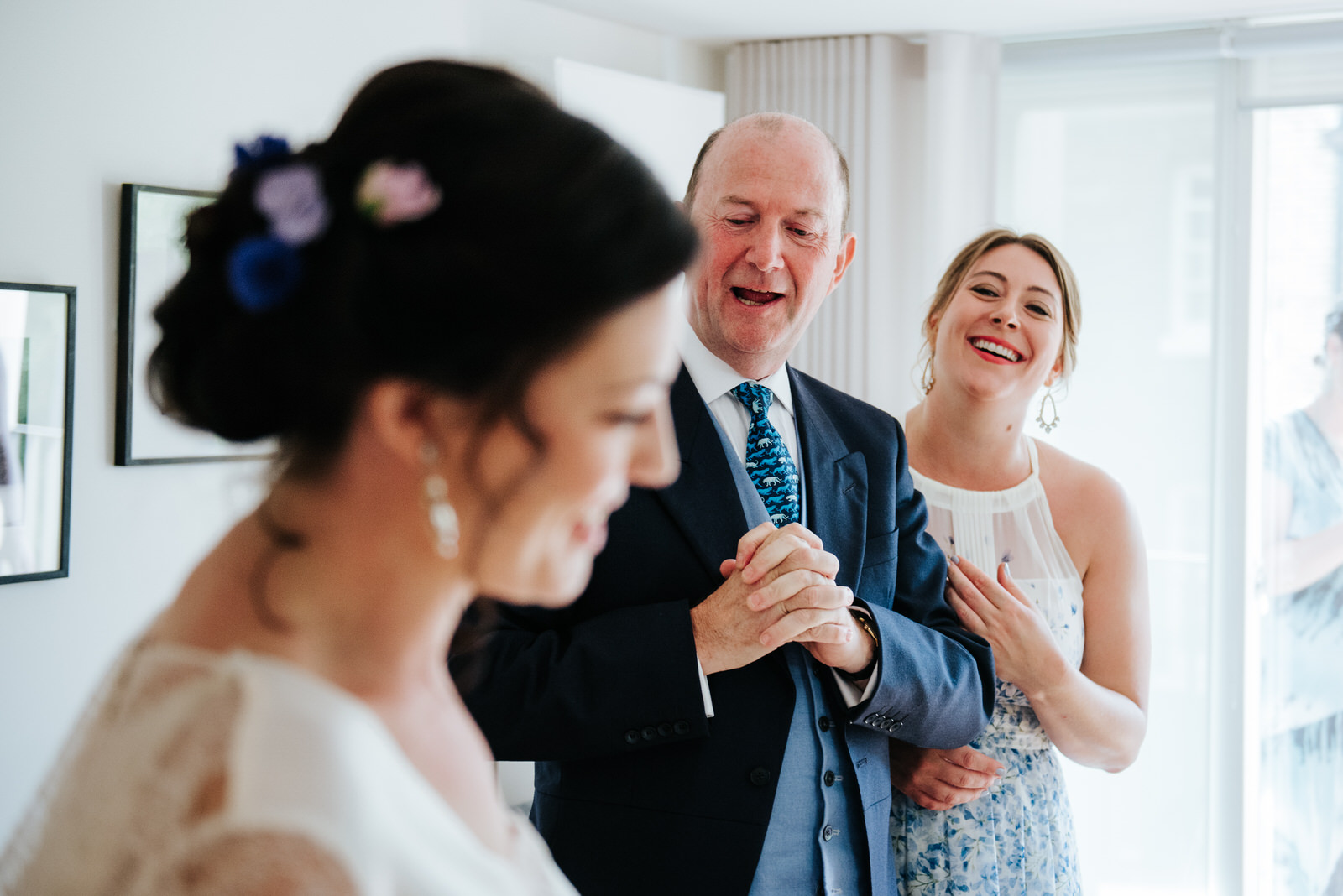 Father of the bride reacts and smiles after seeing her in her dr