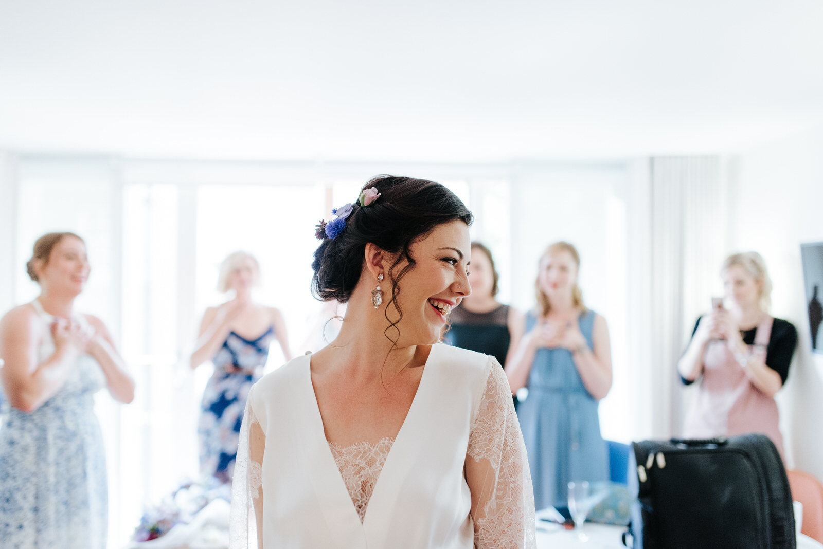 Bride twirls and smiles in her dress in front of bridesmaids