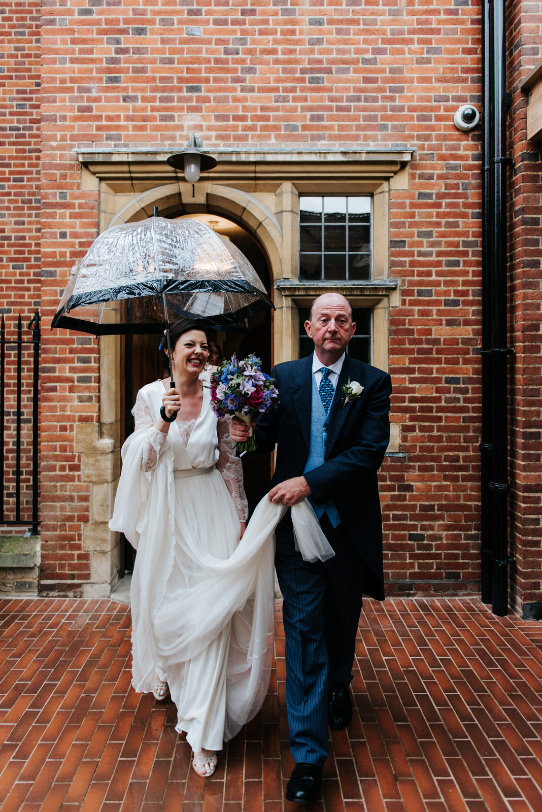 Bride and her father walk towards Jesus College chapel in the po