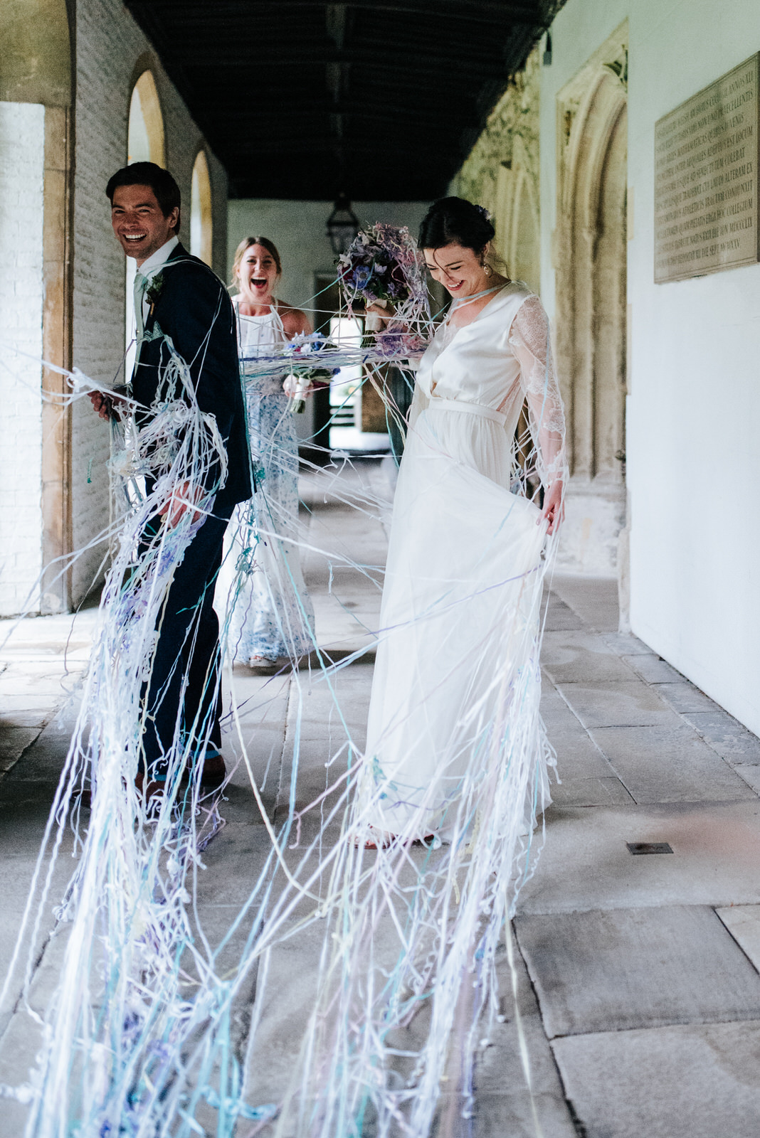 Bride and groom completely covered in strings of confetti as the