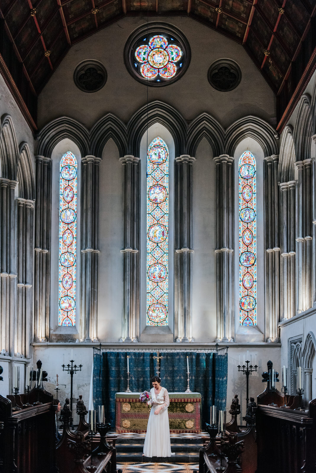 Bride stands under stained glass in Jesus College Chapel in Camb