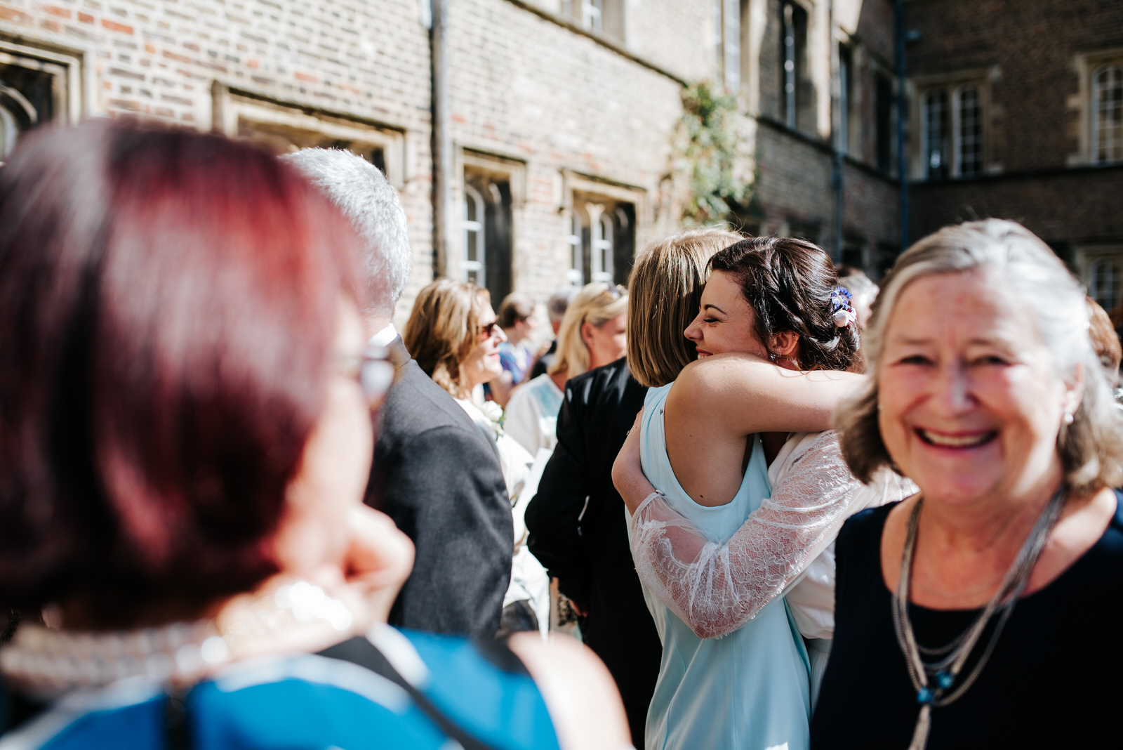 Bride hugs guests as they enjoy wedding reception drinks in firs