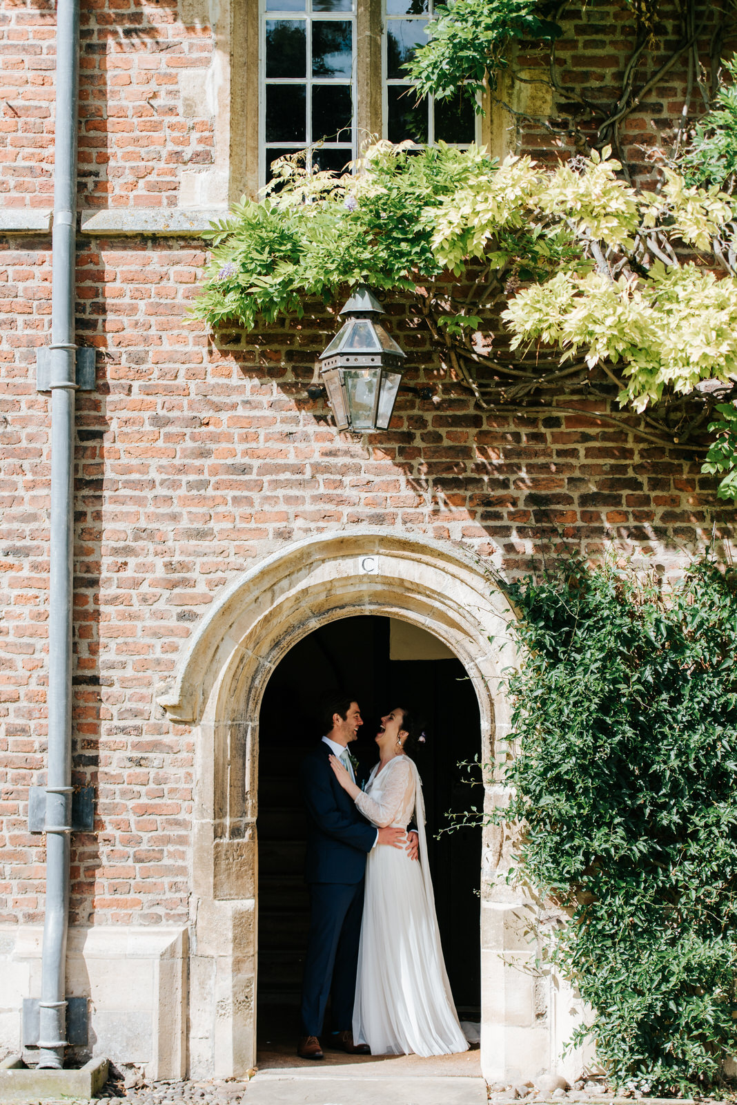 Bride and groom embrace each other under concrete arch at Jesus