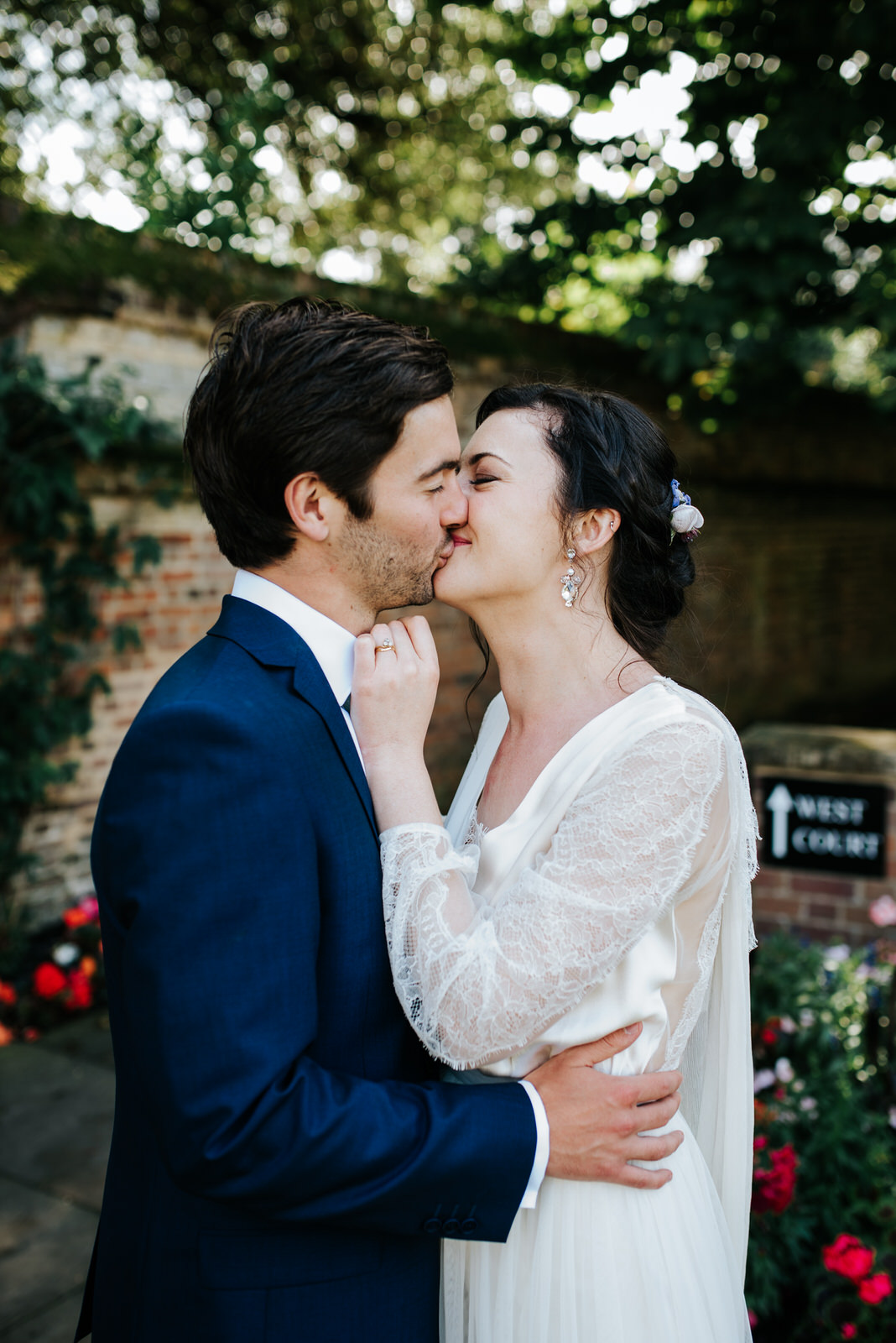 Bride and groom kiss under beautiful green trees during couple p