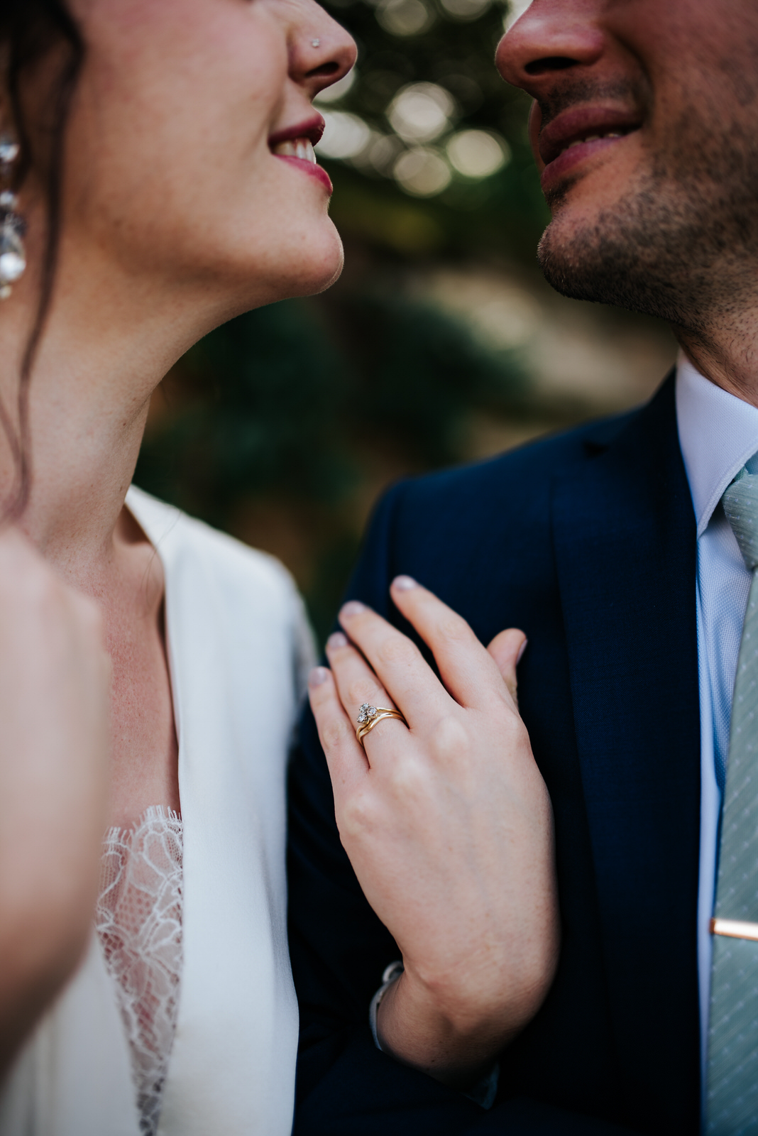 Bride shows off stunning diamond ring as she looks into groom's