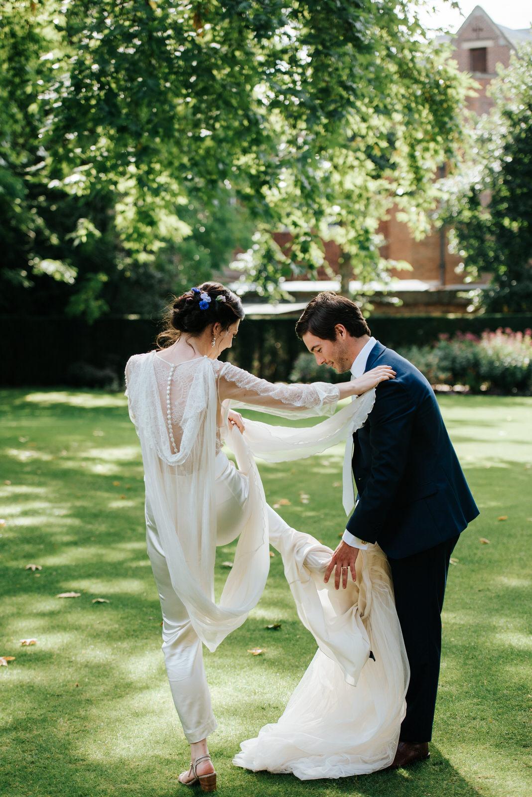 Groom helps bride take off her skirt to reveal wedding dress und