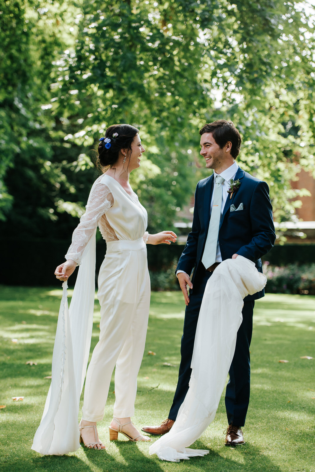Groom smiles at bride as he holds the wedding skirt she has just