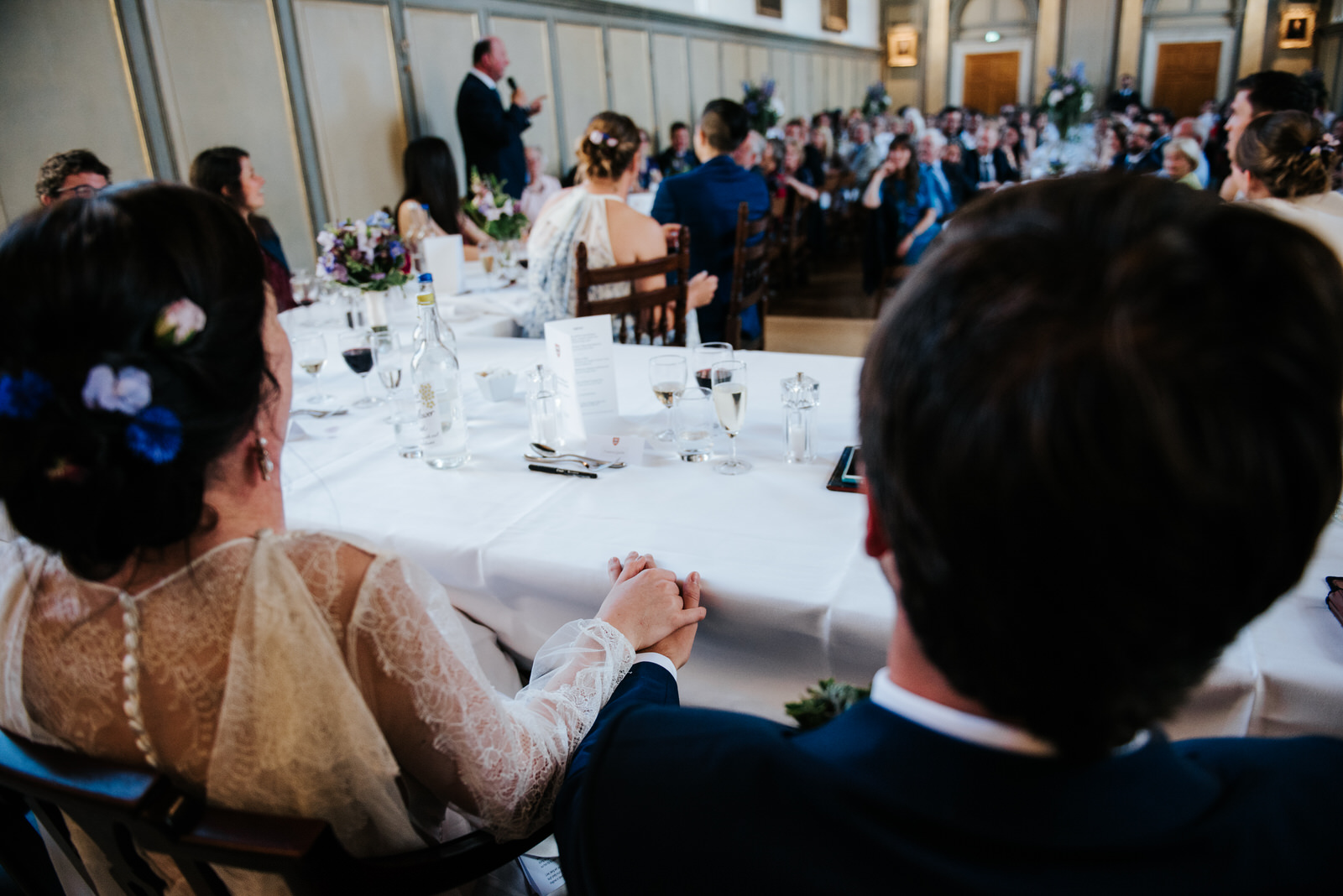 Bride and groom hold hands under the table in romantic moment du