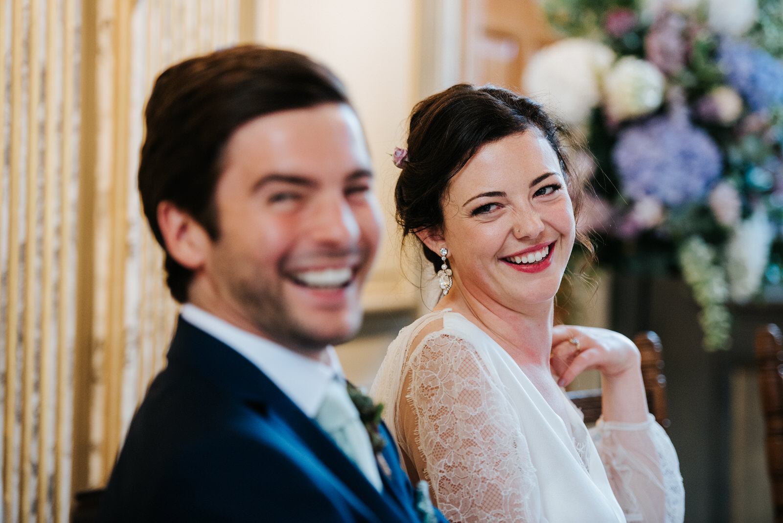 Groom and bride smile with teeth and look into camera