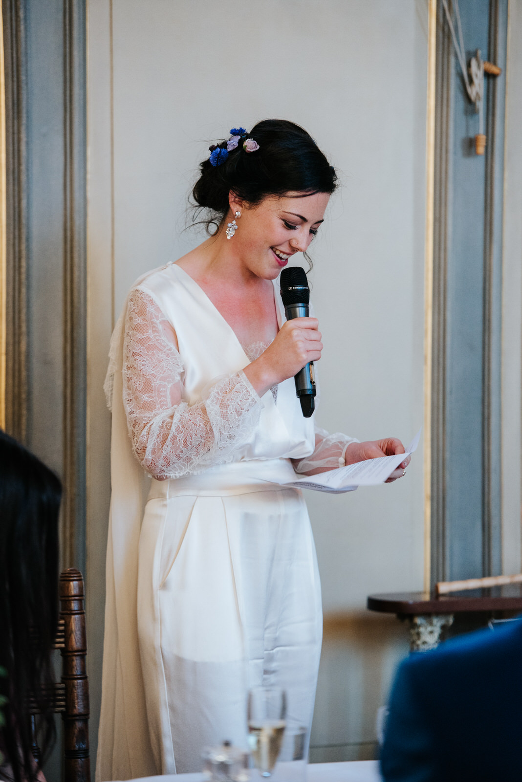 Bride reads from paper as she delivers her own wedding speech