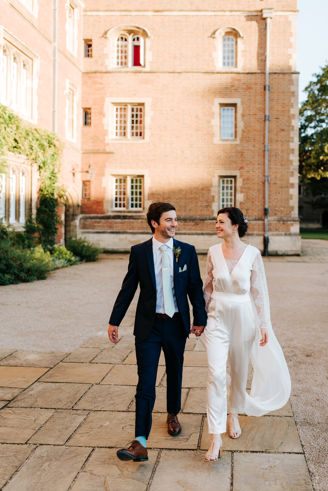 Bride and groom walk hand in hand through Jesus College Chapel C