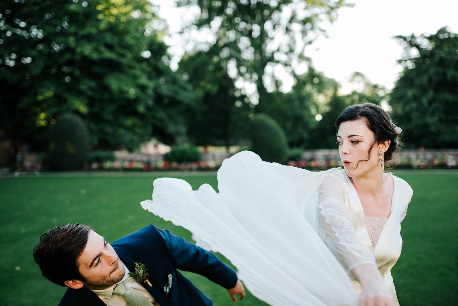 Bride swings her dress at groom pretending it is a superhero cap