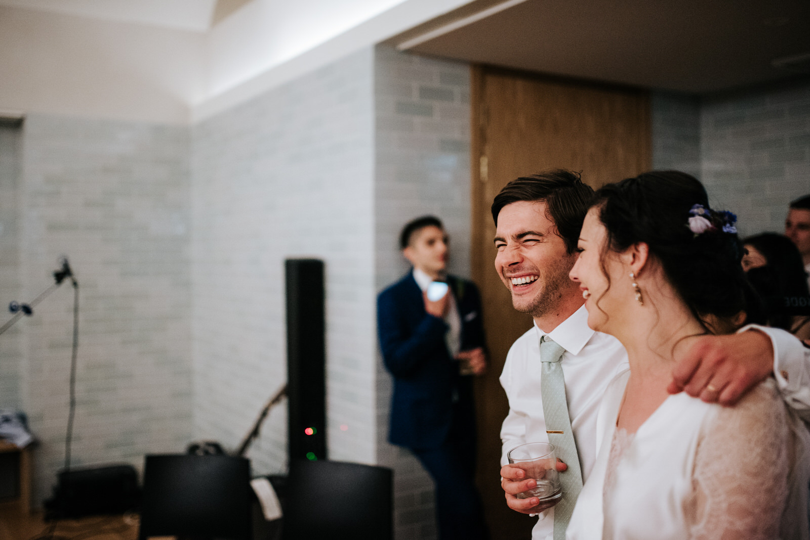 Groom reacts to speeches by squeezing bride and smiling