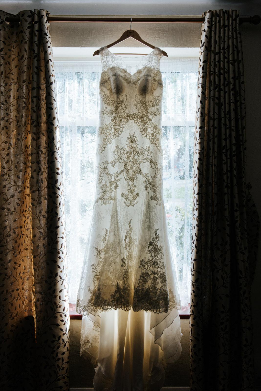 Bride's dress hangs in front of window