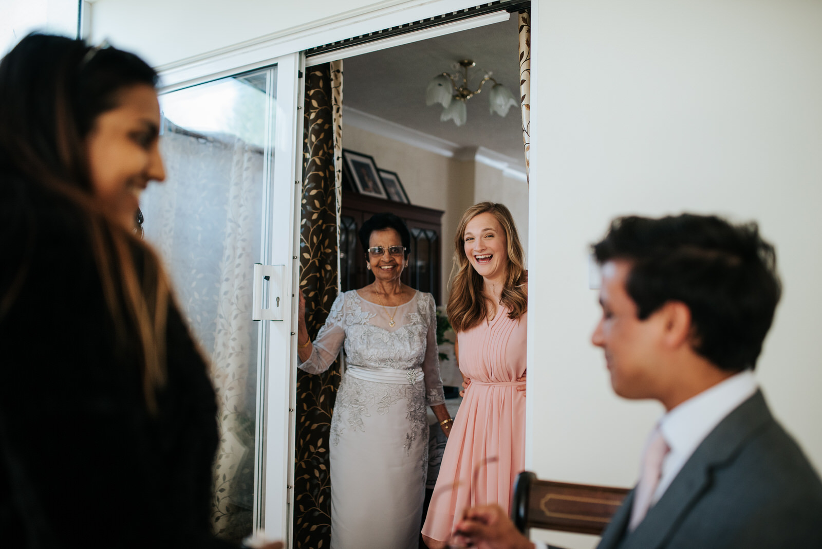 Girlfriend of bride's brother smiles as he has his hair done