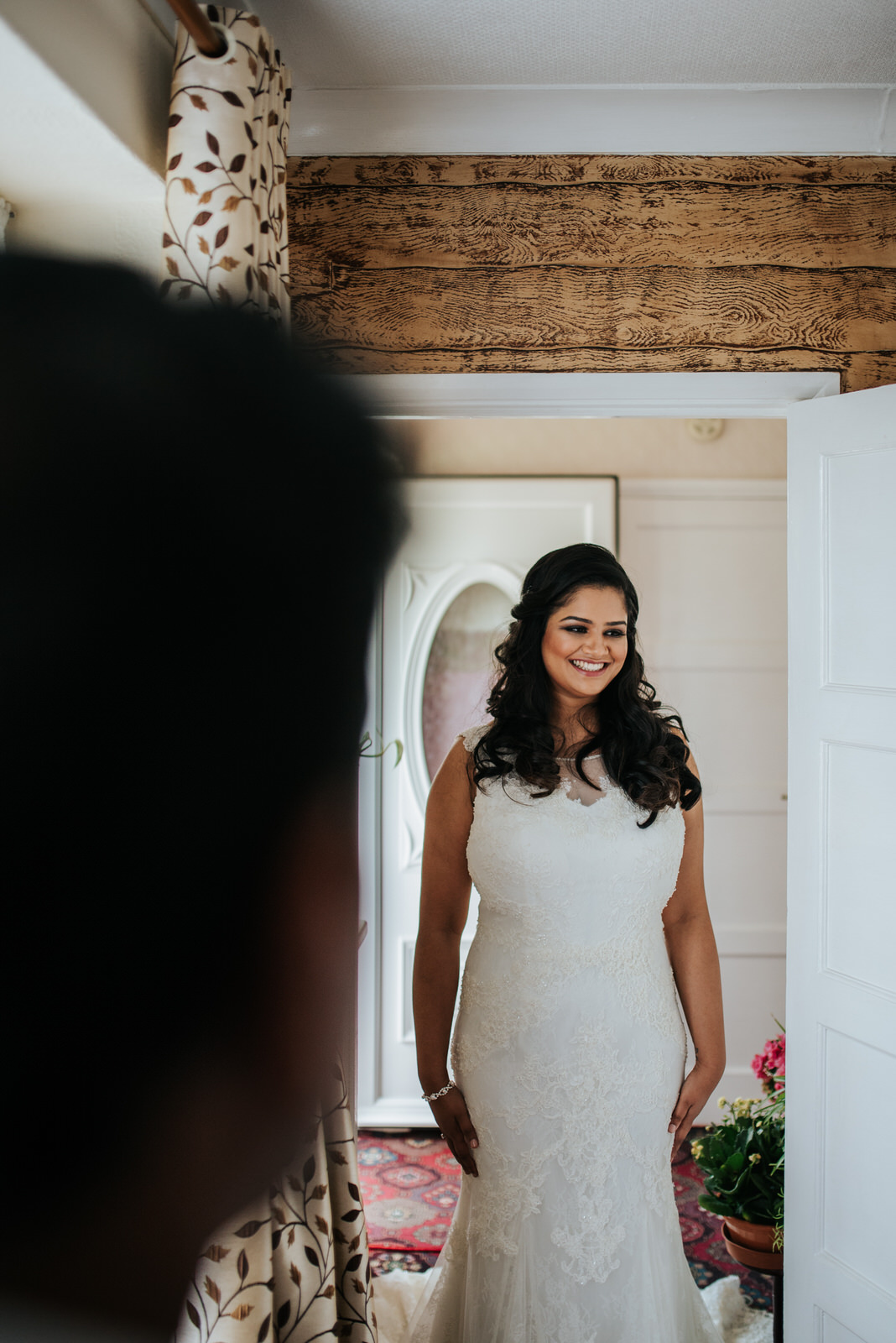 Bride smiles as she stands in front of family in her wedding dre