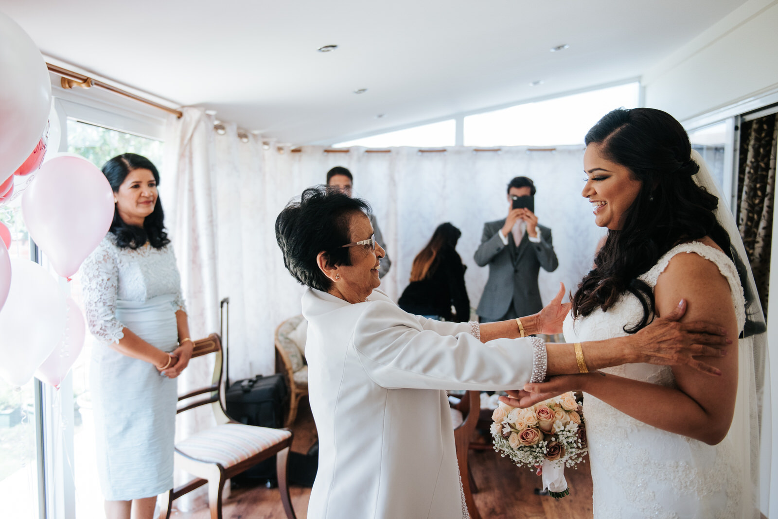 Bride receives blessing from her grandmother while both smile