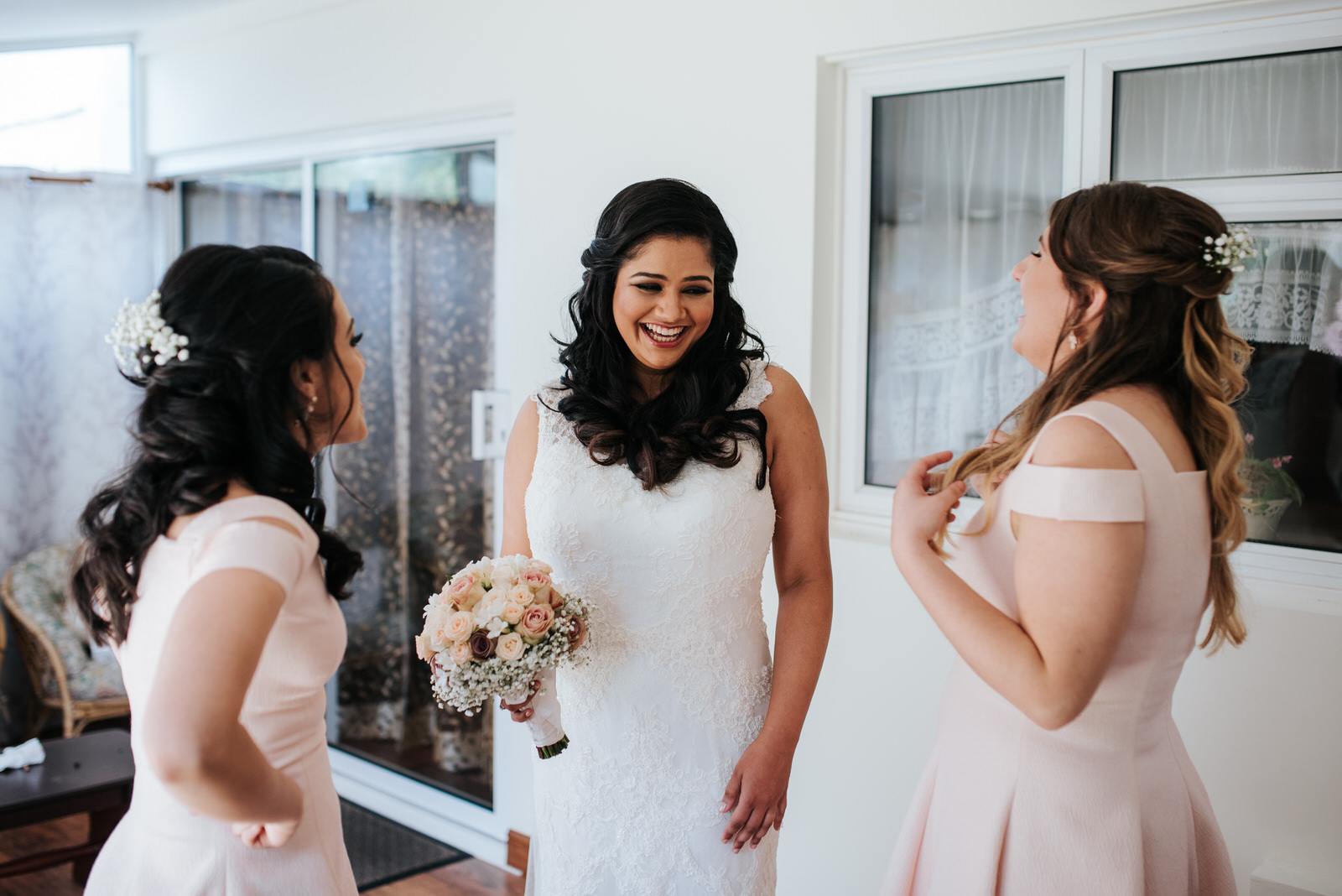 Bride shares a joyous moment with two bridesmaids before departi