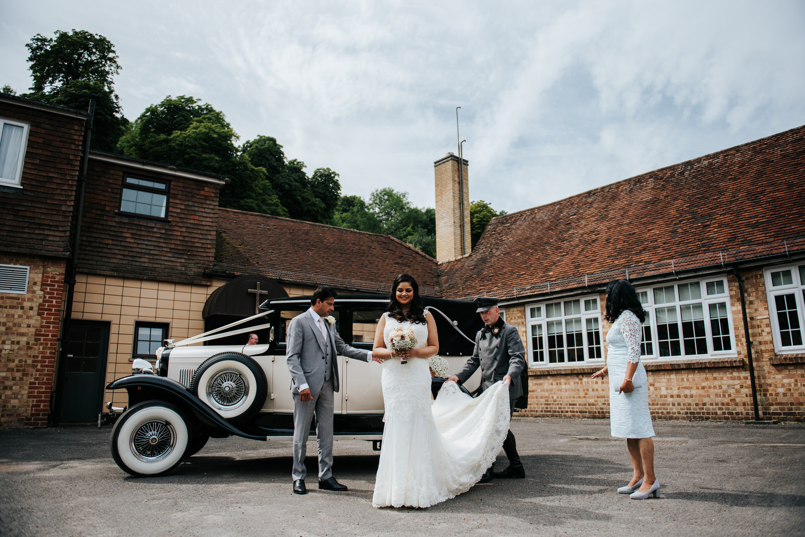 Bride stands in front of antique car ready to enter the wedding