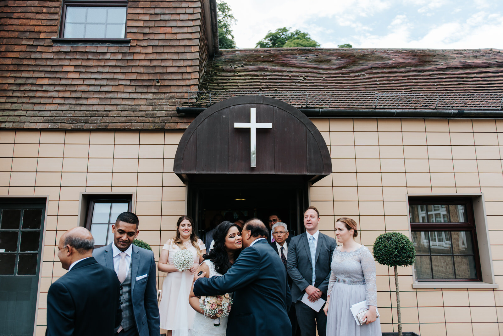 Bride and groom welcome guests outside chapel after ceremony