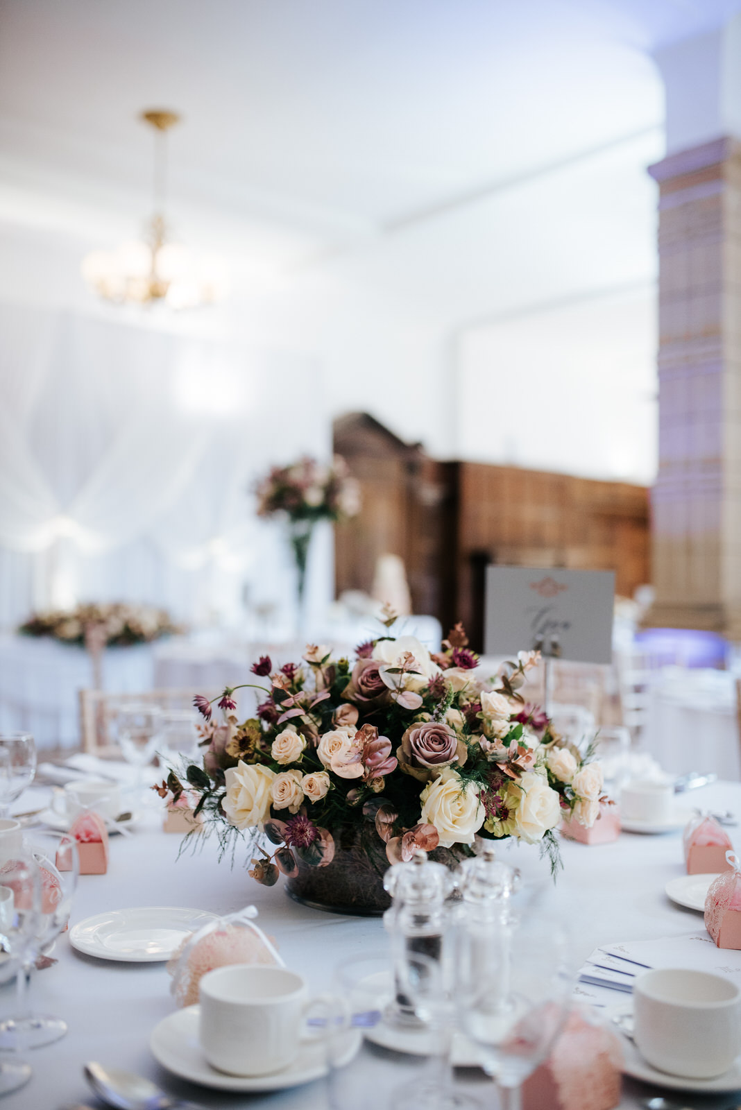 Close-up photo of rose flower centrepiece on tables inside Woldi