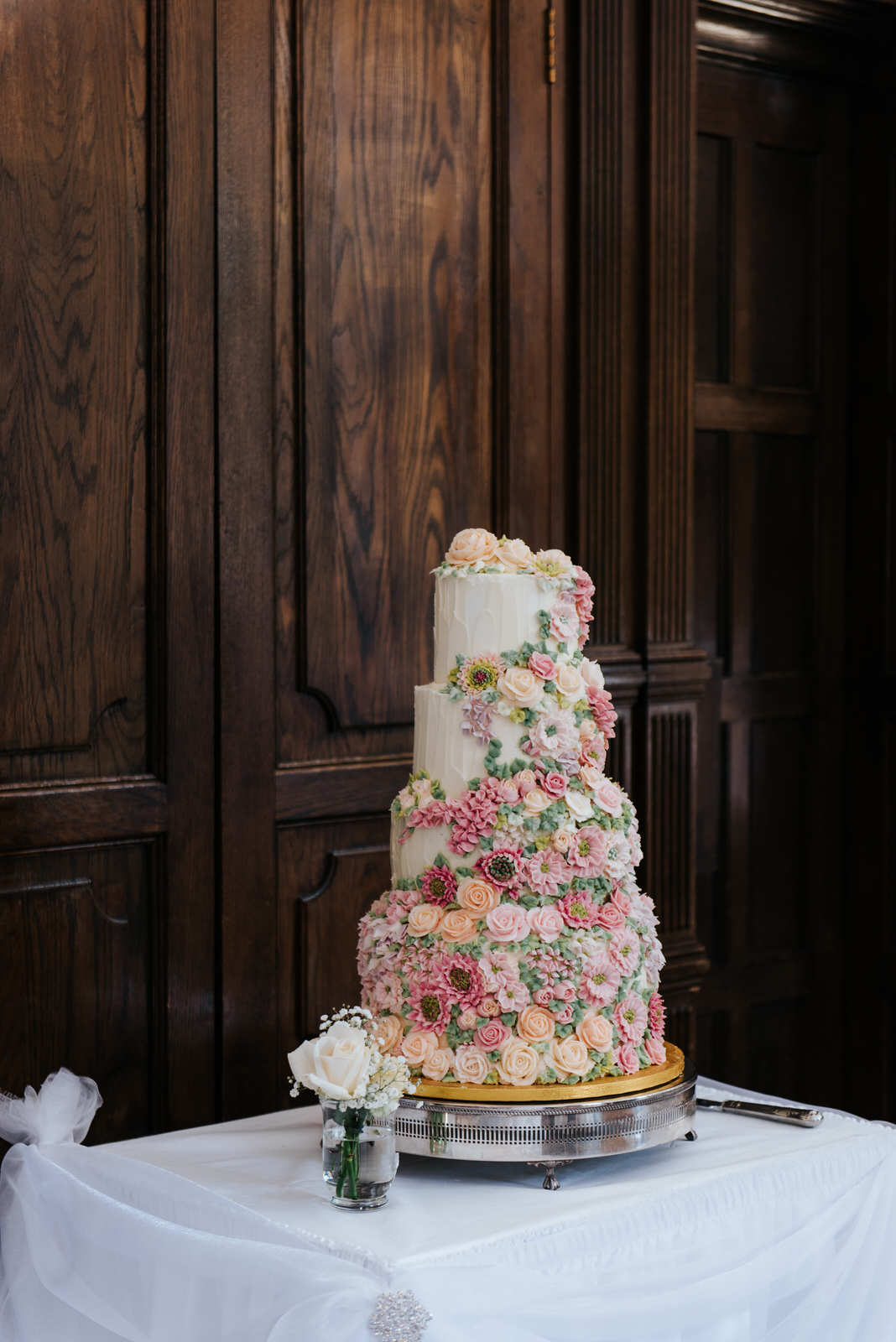 Beautiful, four-tier wedding cake decorated with roses and flowe