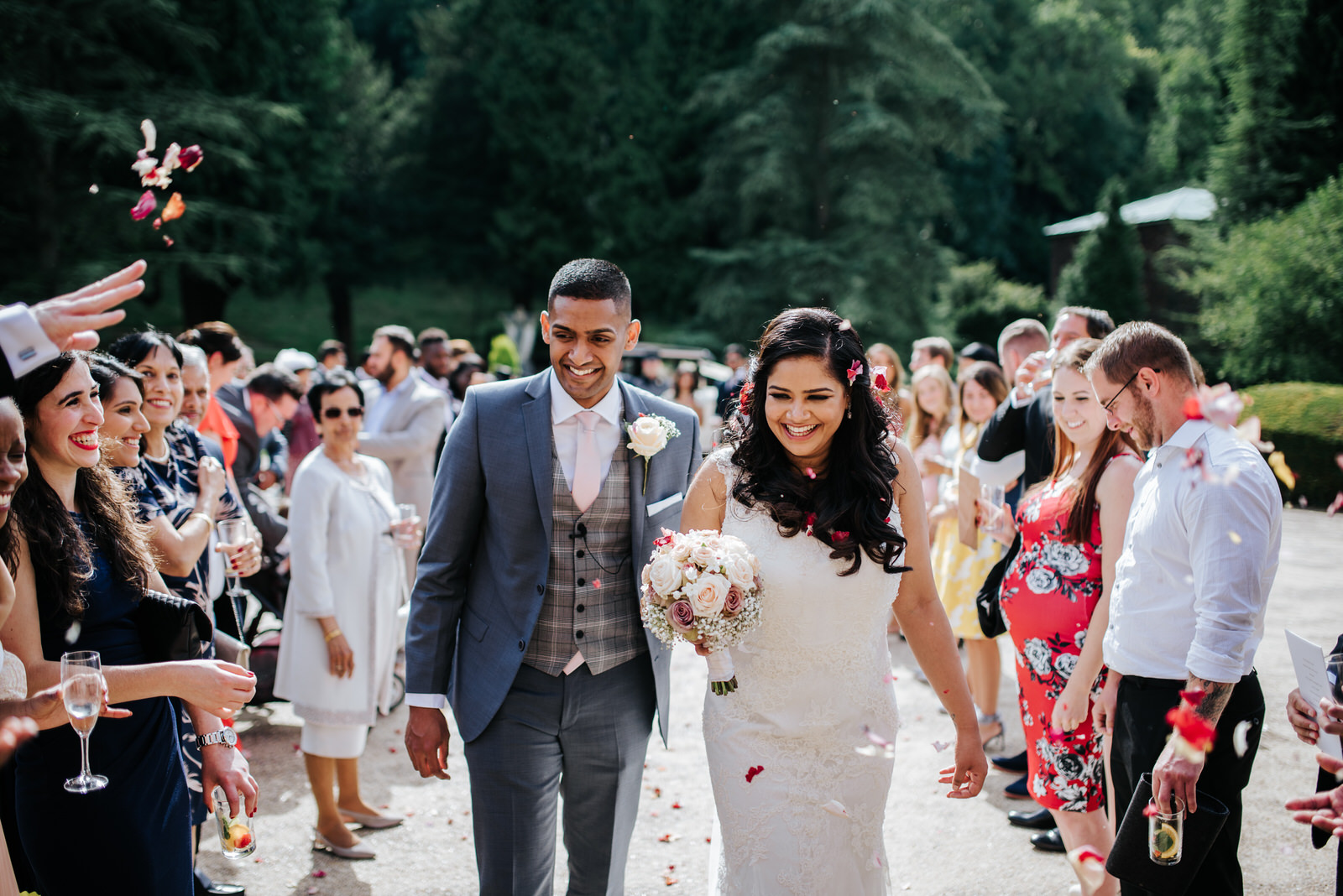 Bride and groom walking down tunnel of guests at Woldingham Scho