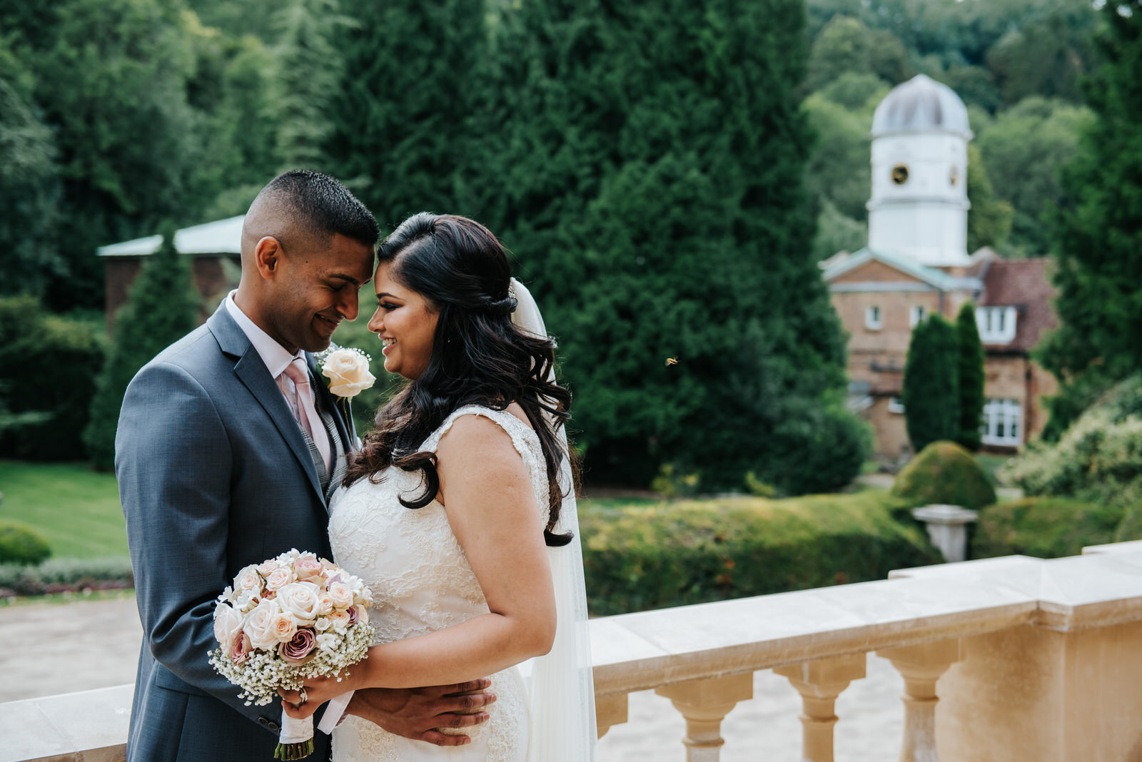 Bride and groom touch foreheads and smile during couple photos