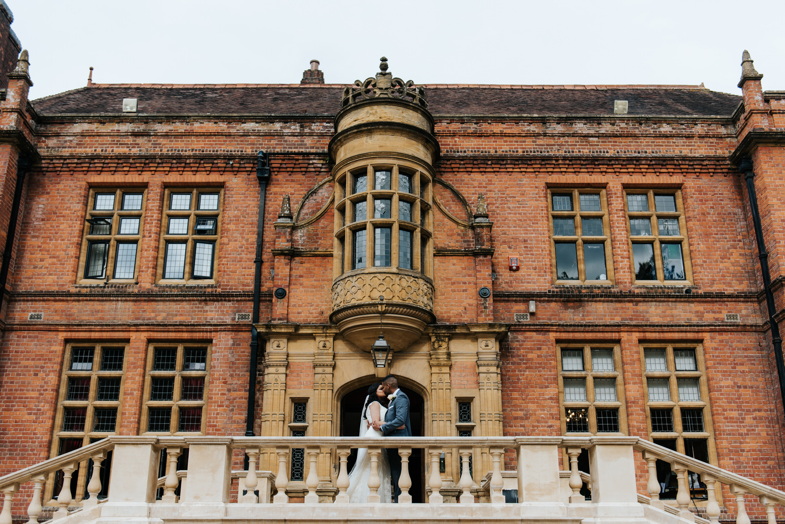 Bride and groom kiss in front of beautiful main building at Wold