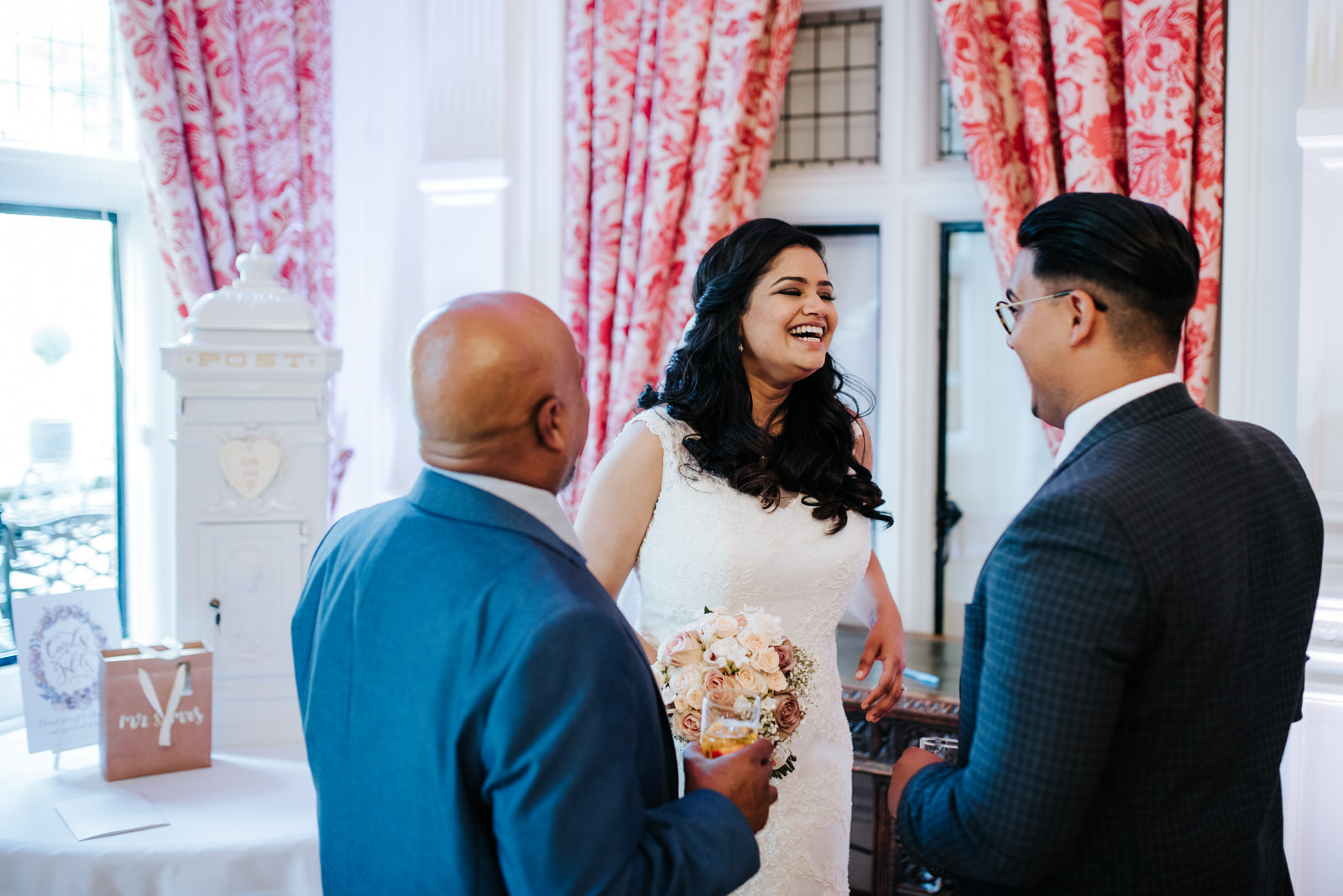 Bride smiles and jokes with family members during wedding recept