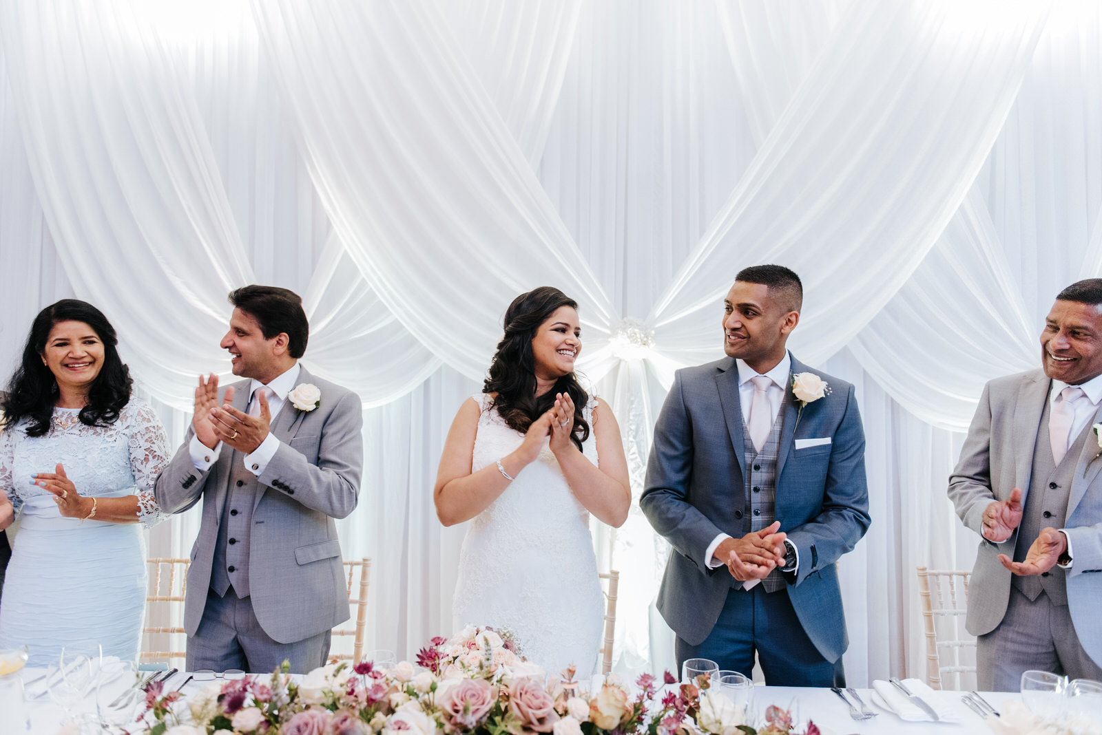 Bride and groom clap at head table as everyone welcomes them int