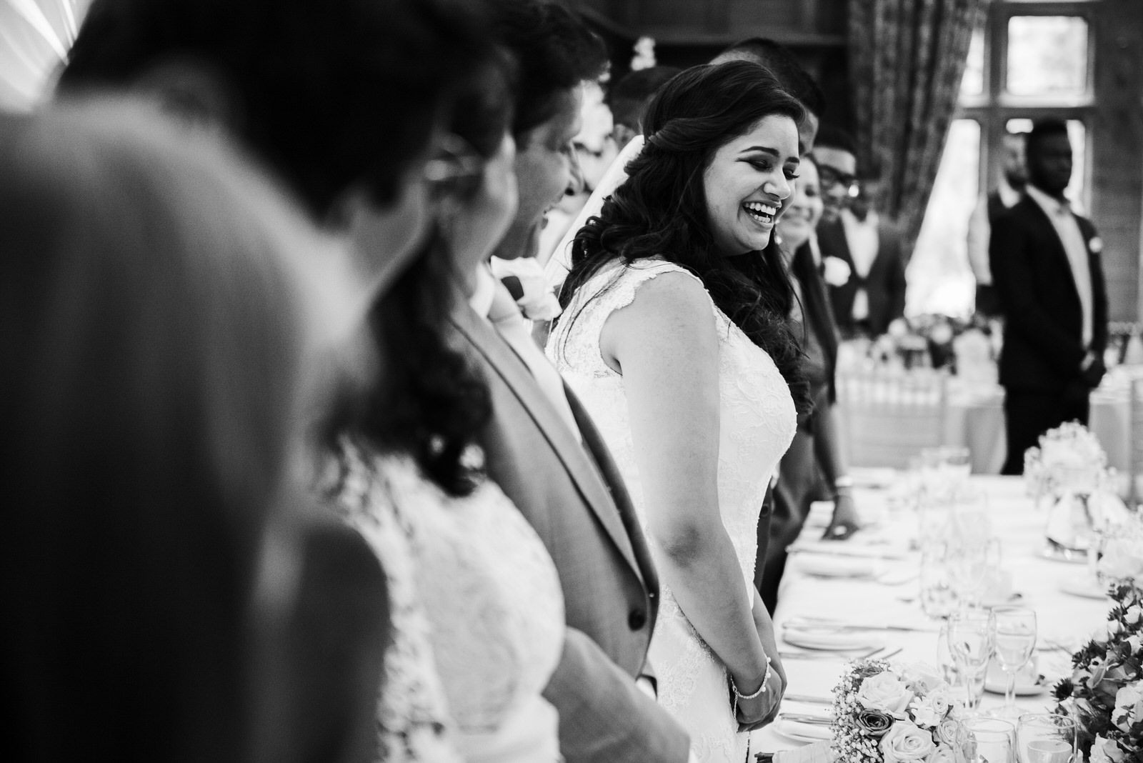 Bride smiles in black and white photo as brother delivers speech
