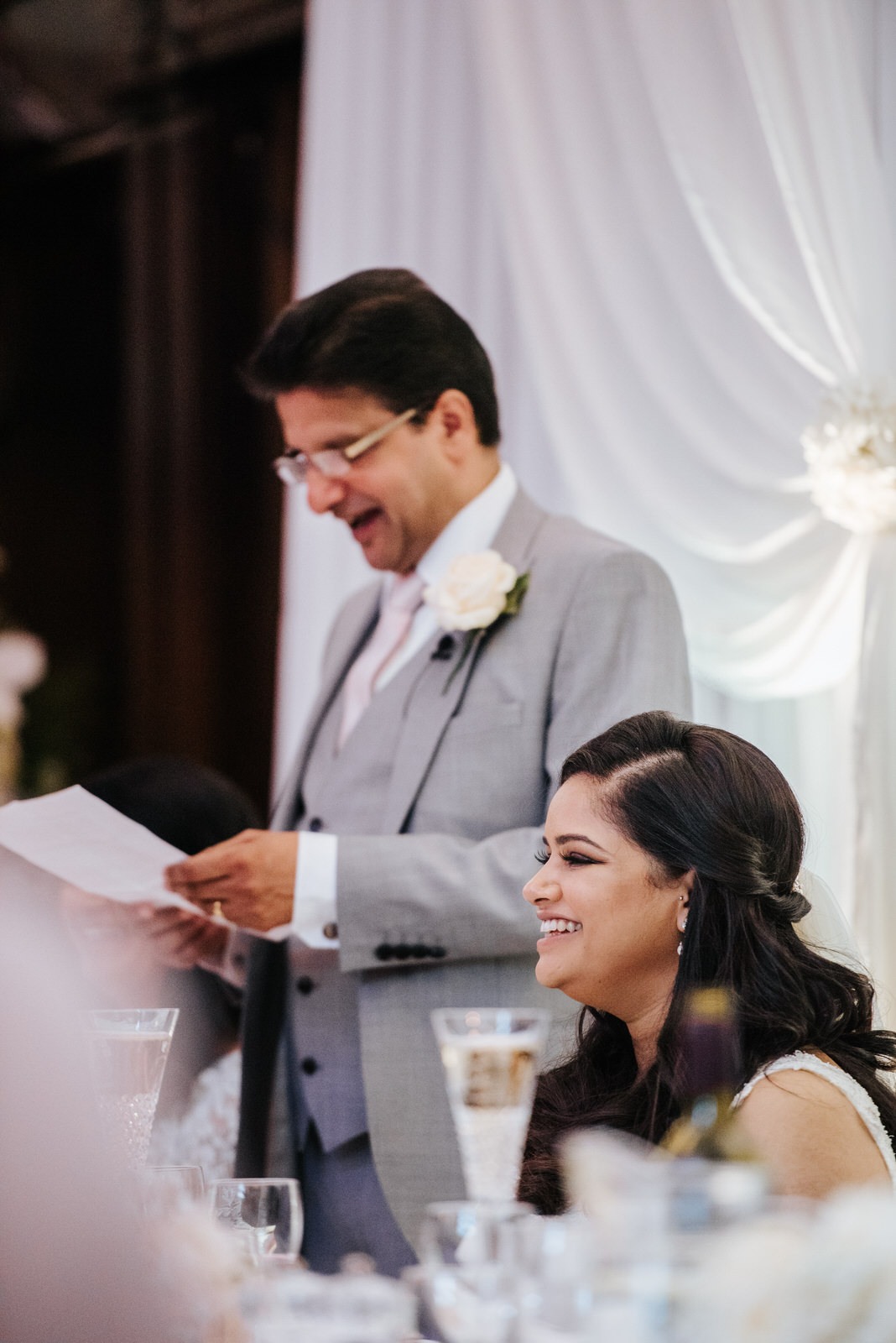 Bride smiles and looks veyr happy as her father delivers his wed