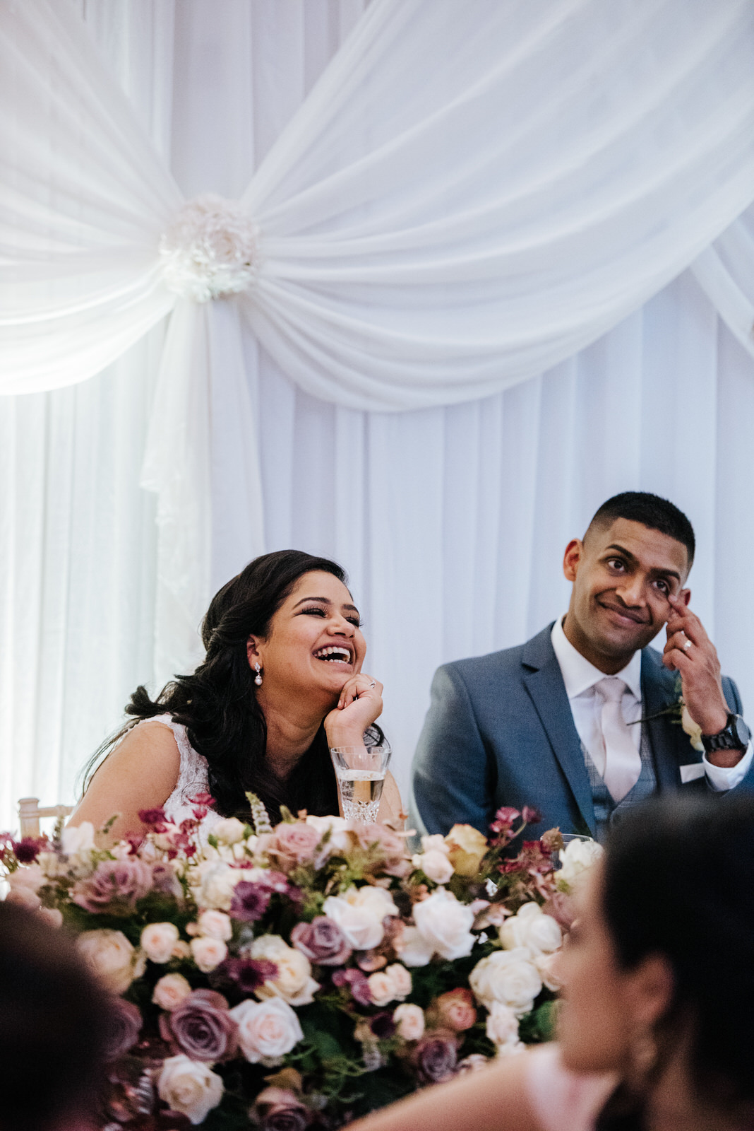 Bride and groom laugh while speaking to guests