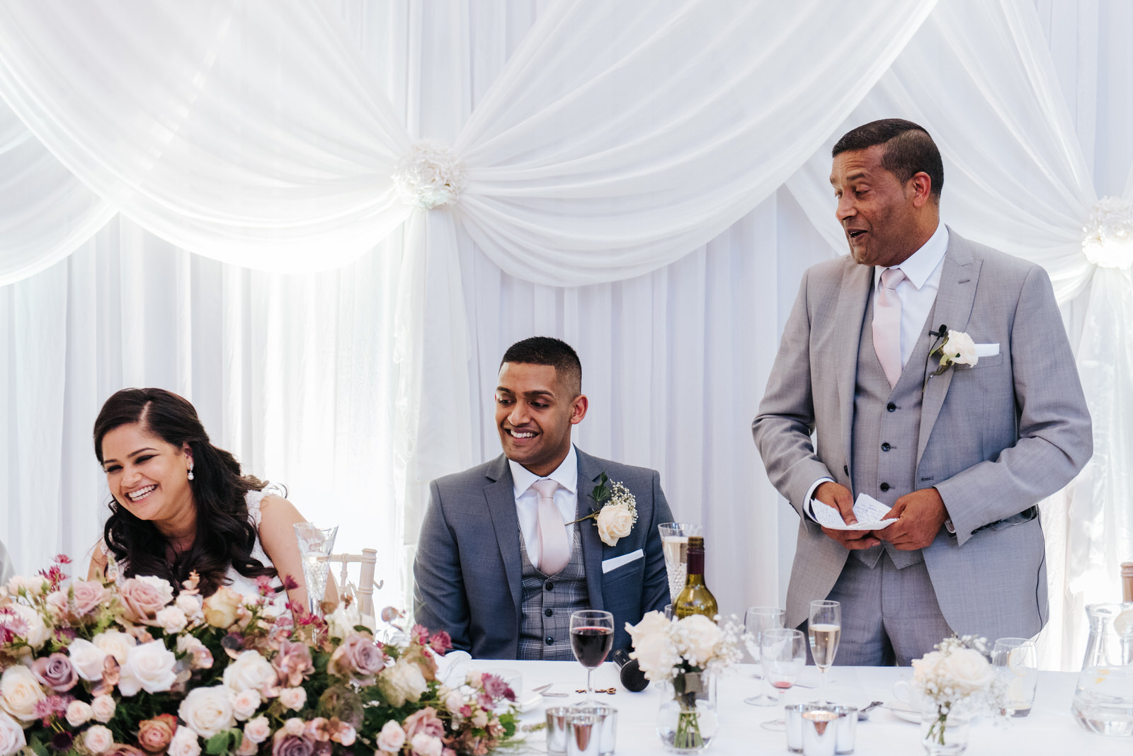 Father of the groom delivers his speech as bride and groom sit a