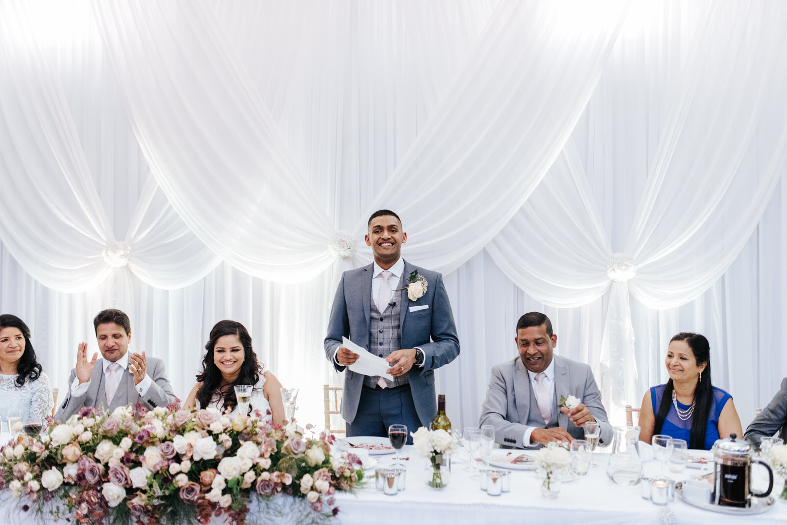 Groom stands up and begins his speech
