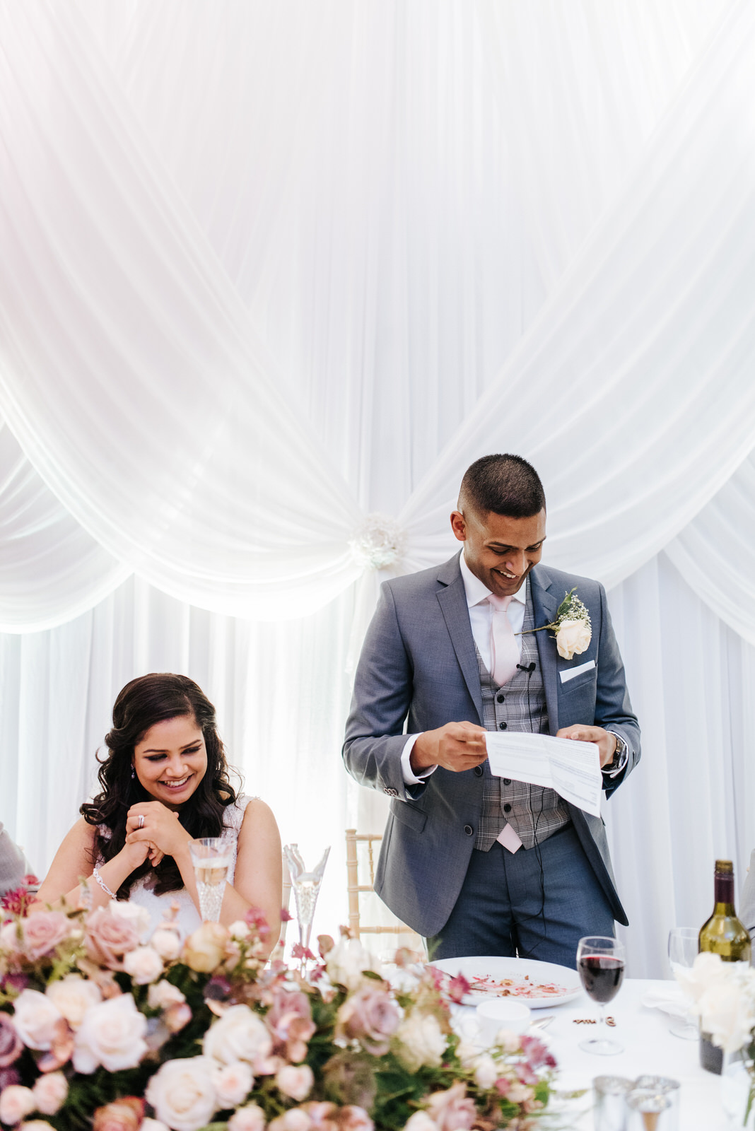 Groom smiling and laughing with his bride as he delivers his spe