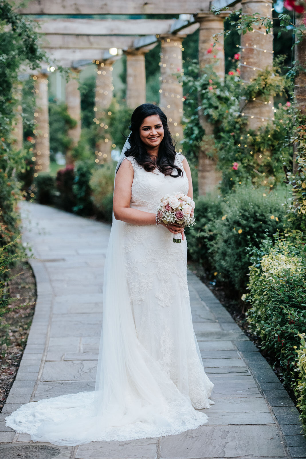 Portrait of bride as she stands outside in the garden at Wolding