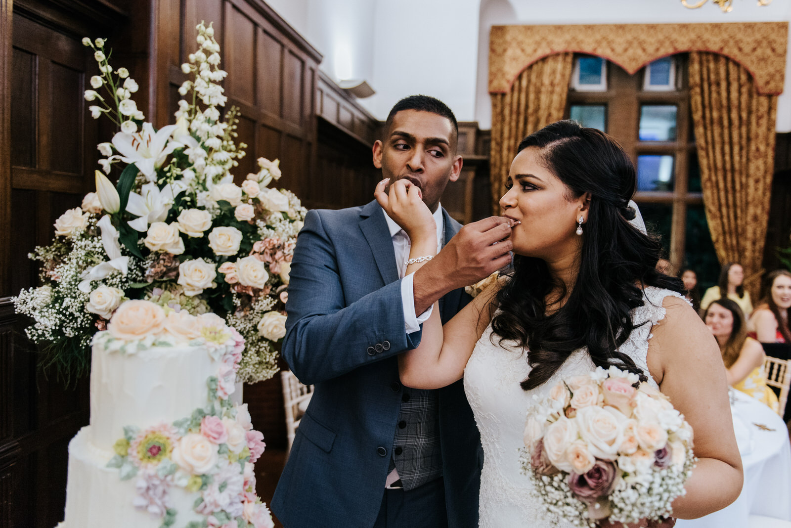 Bride and groom make funny faces as they feed each other the cak