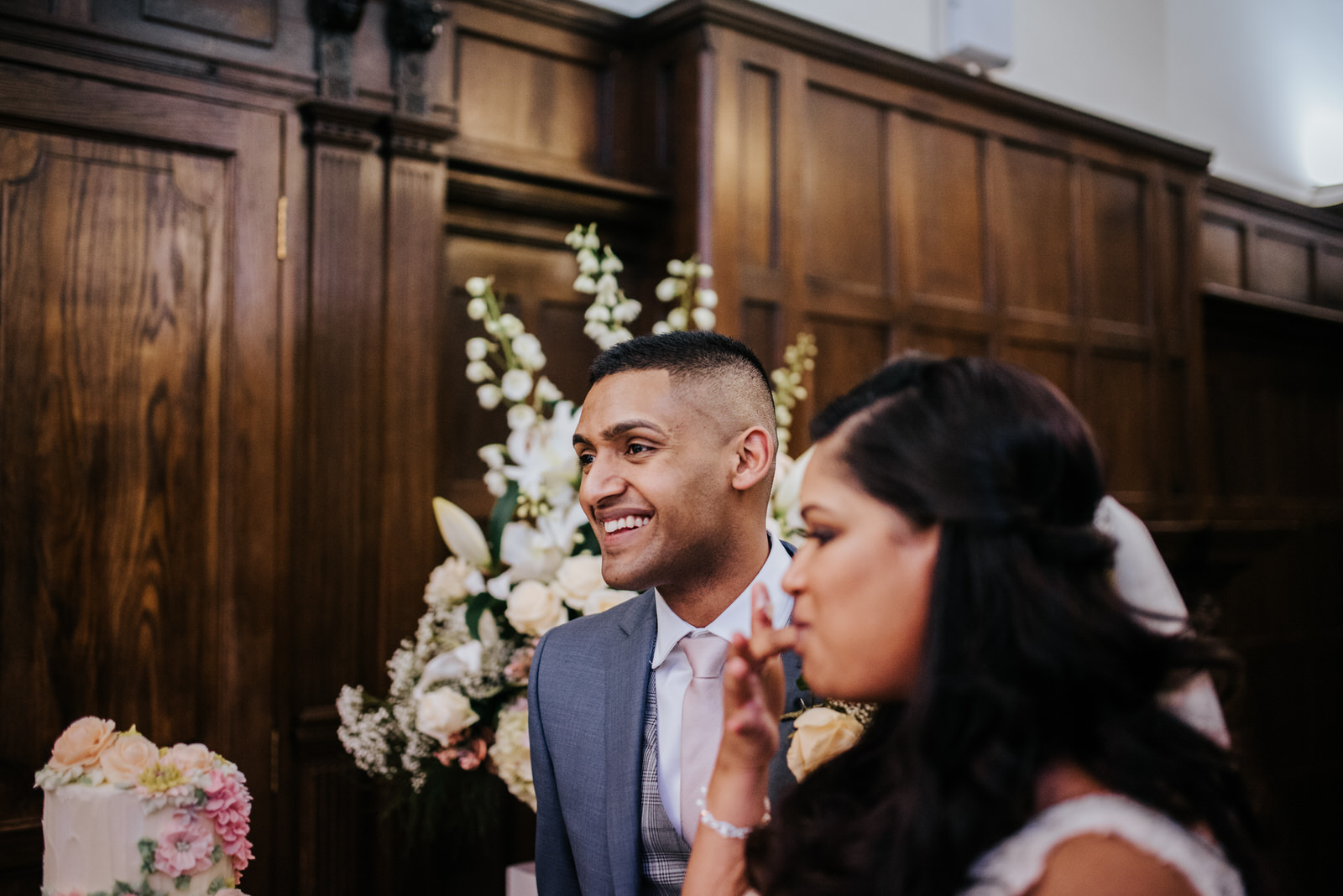 Groom smiles after he finishes eating a piece of cake