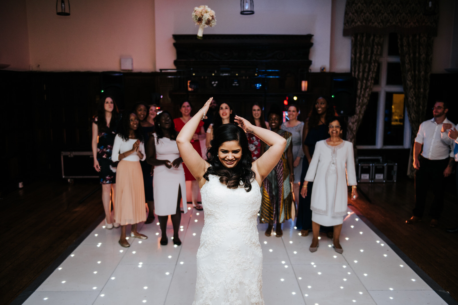 Bride throws her boquet at friends inside Woldingham School