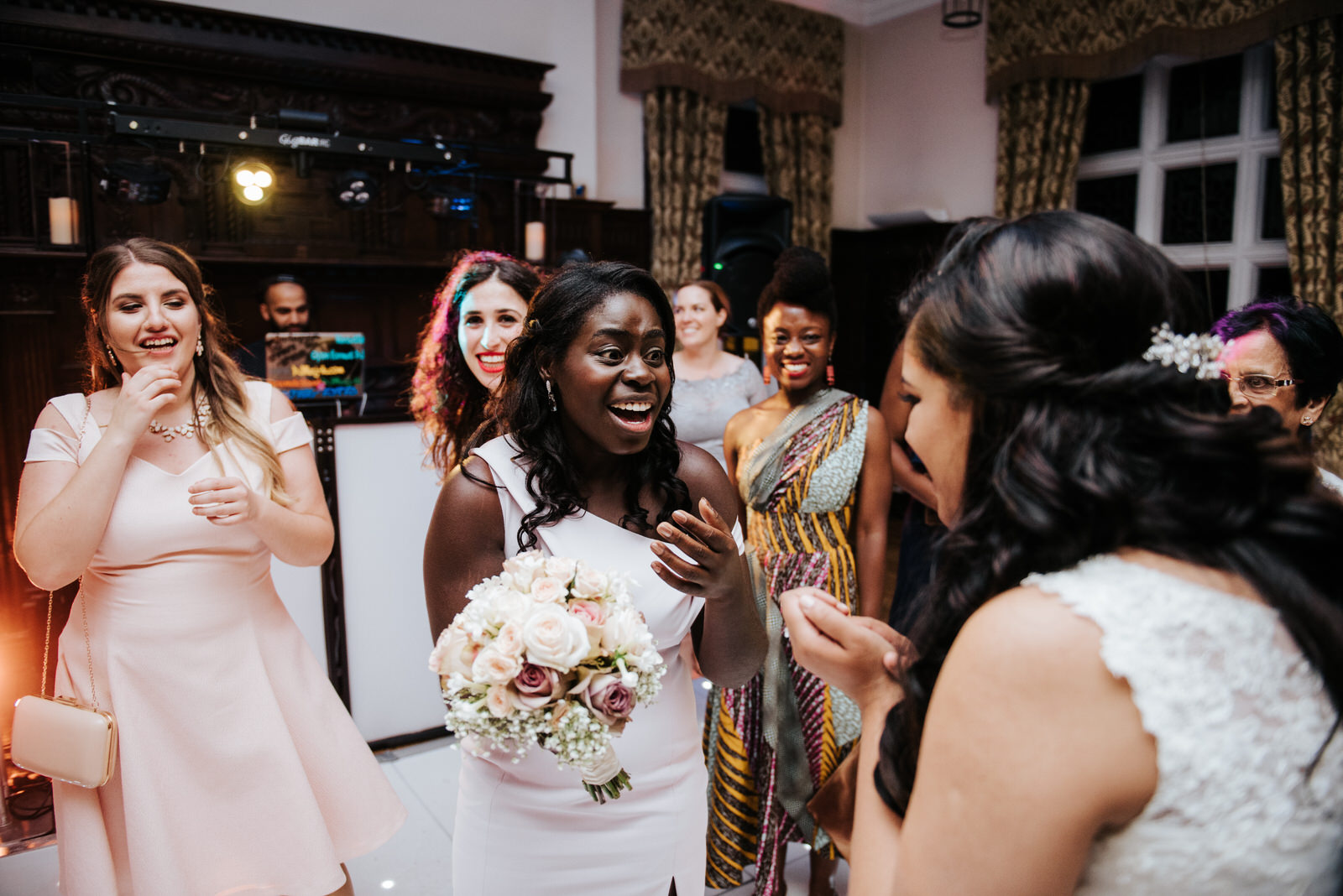 Guest holding bouquet looks and smiles at bride after grabbing i