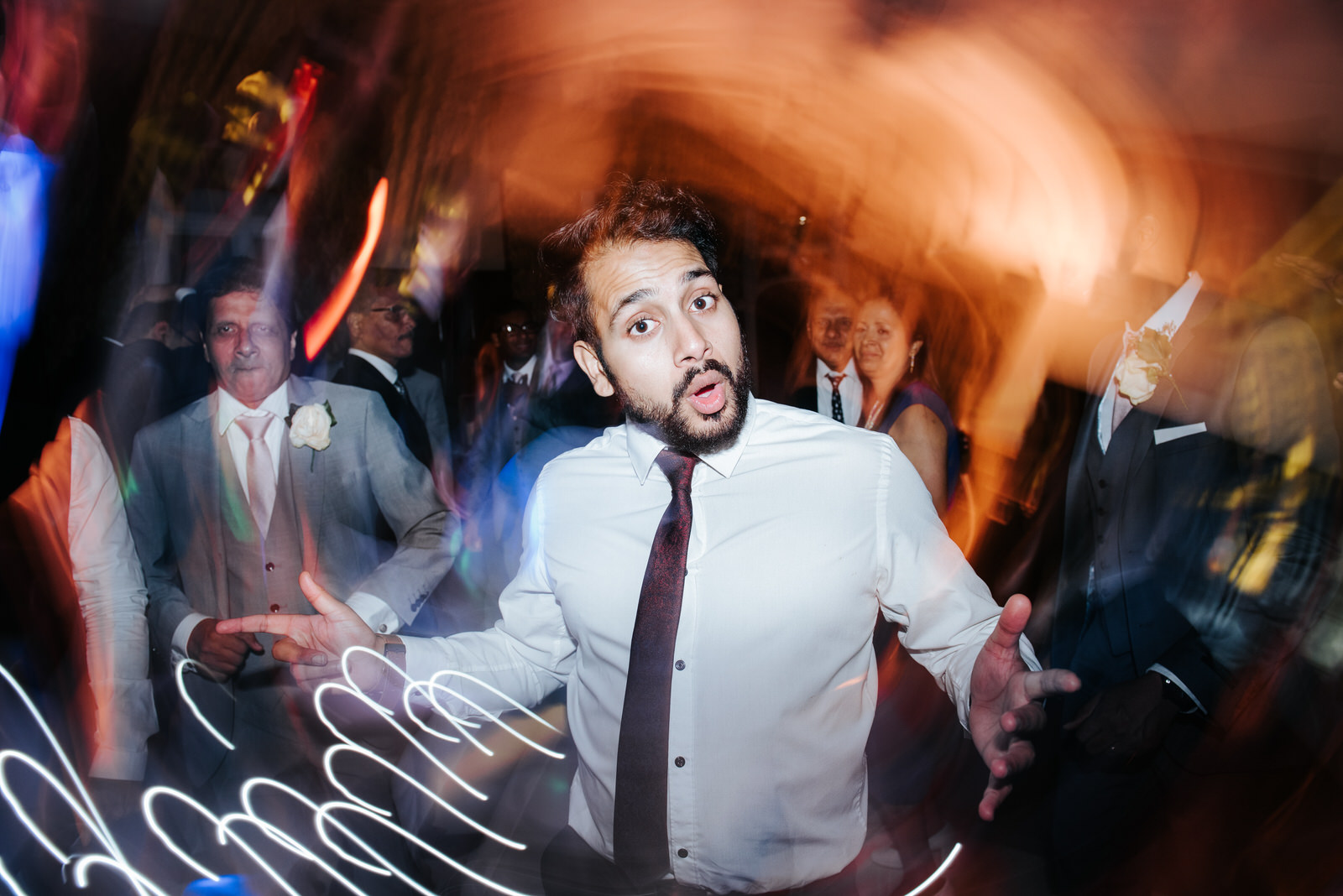 Guest dances under discolights during wedding party