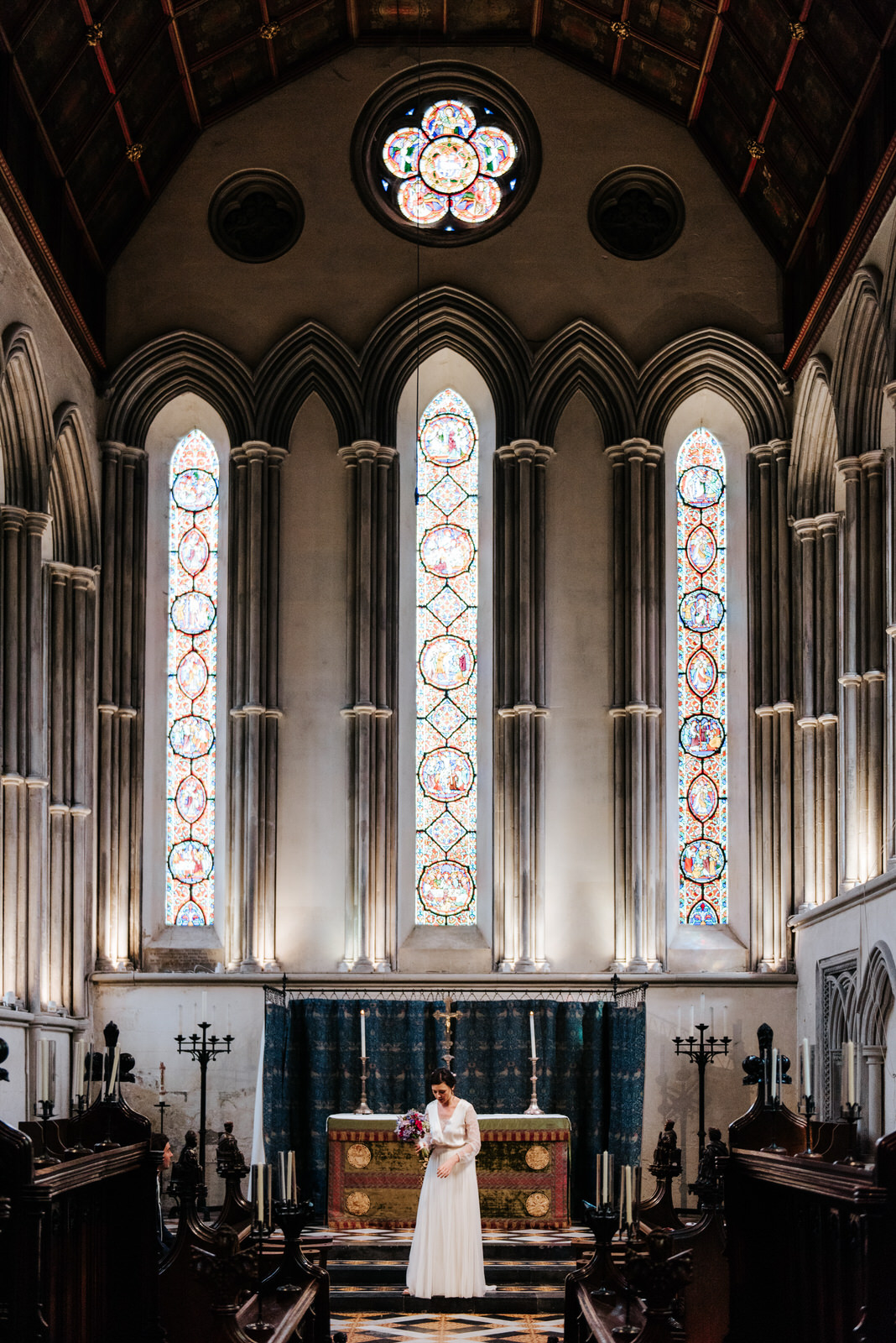 Bride stands under stained glass at chapel in Jesus College Camb