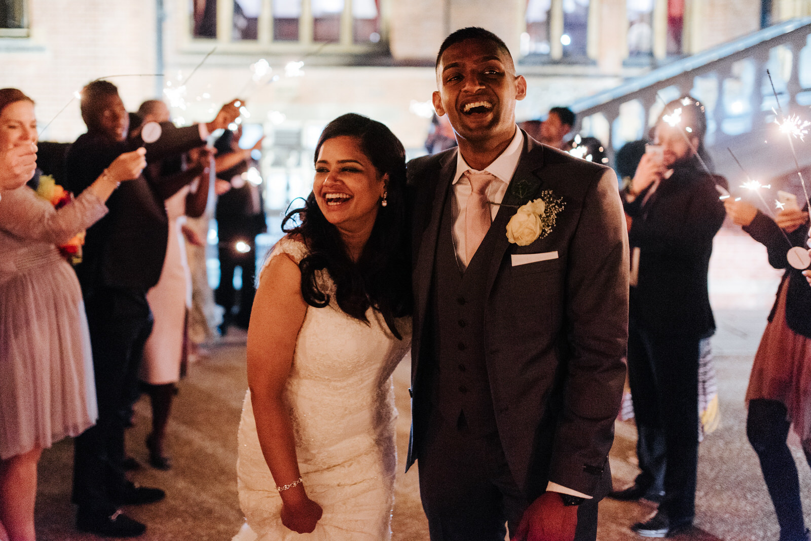 Bride and groom smile as they walk out during sparkler exit at W