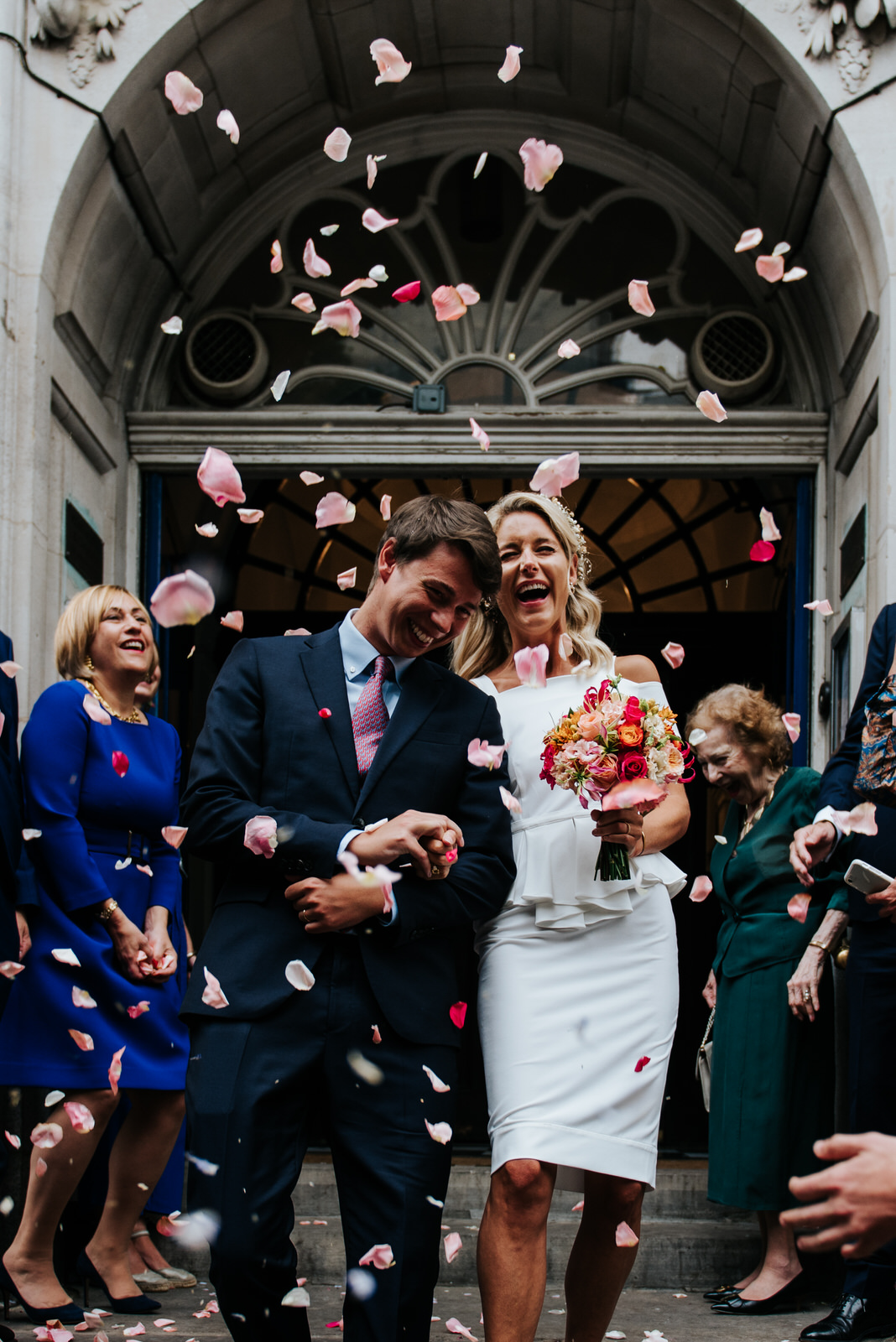Bride and groom laugh as they exit Chelsea Old Town Hall after C