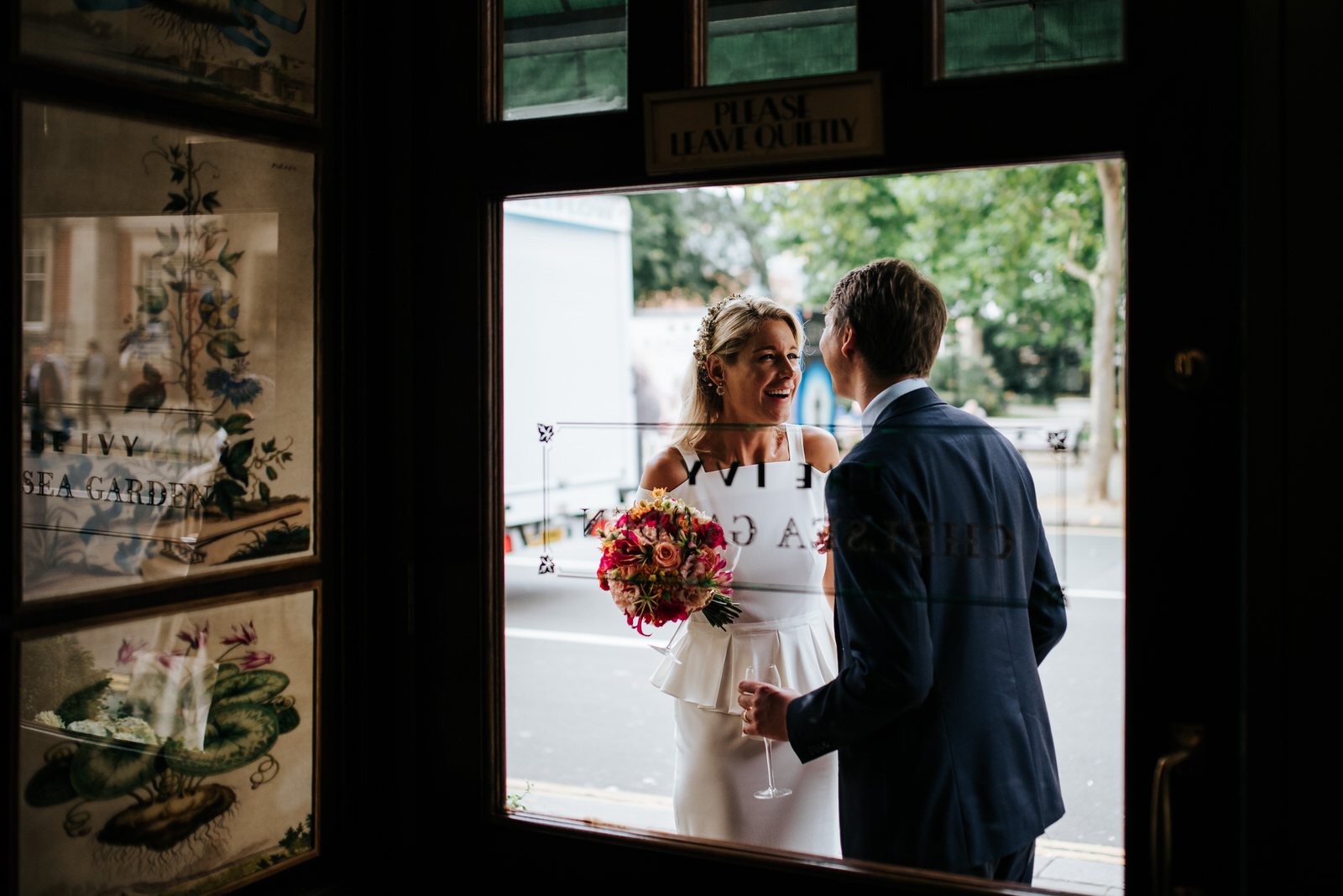 Bride and groom smile at each other in front of The Ivy Chelsea